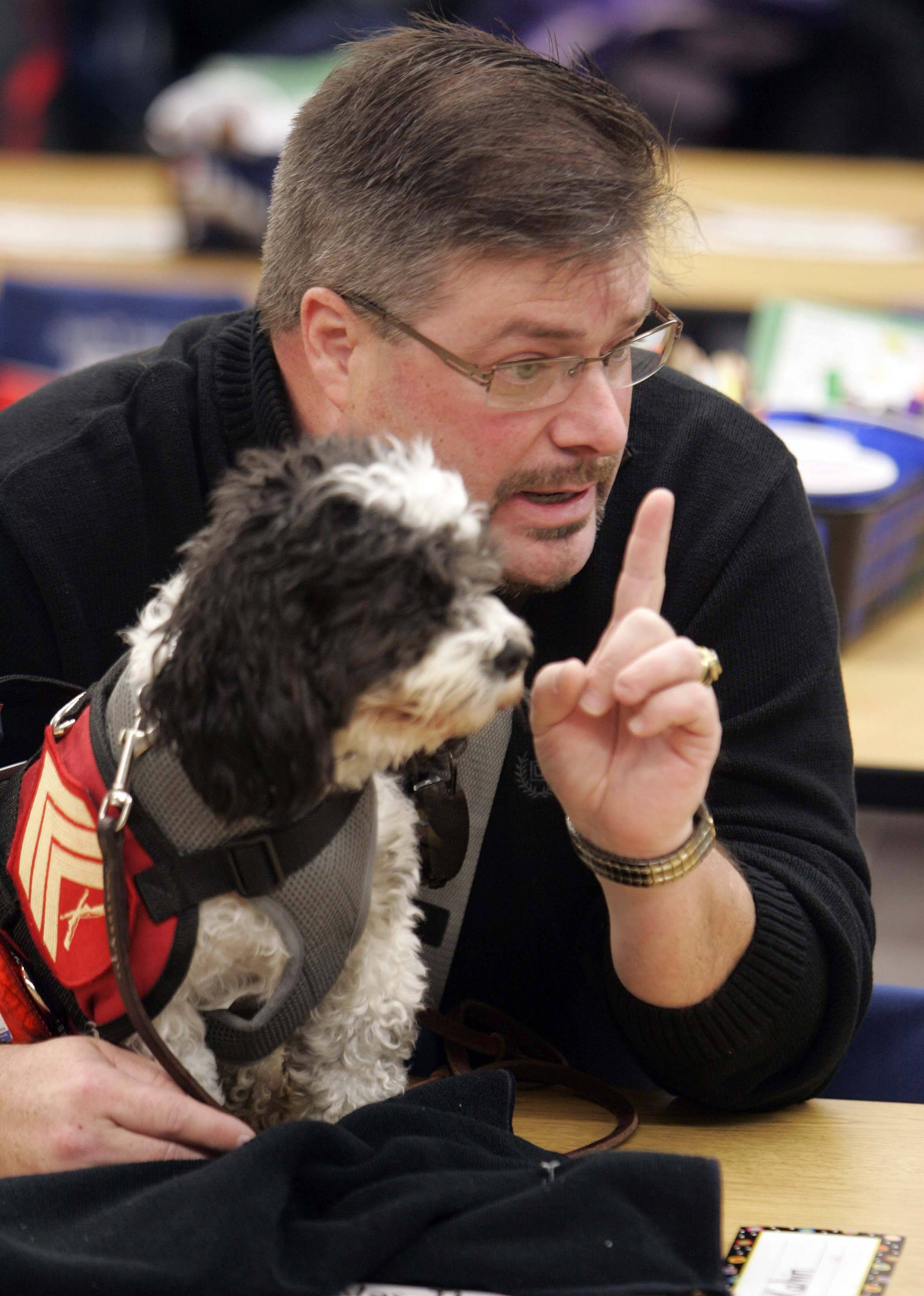 Dan Sauer of Hampshire, talks to Caitlin Berry's kindergarten class at Hampshire Elementary School where he was the class's guest veteran Nov. 10. Sauer, a former sergeant in the Marines, has PTSD and has been working with Chloe, a 17-pound service dog who once almost ended up on a shelter's kill list.