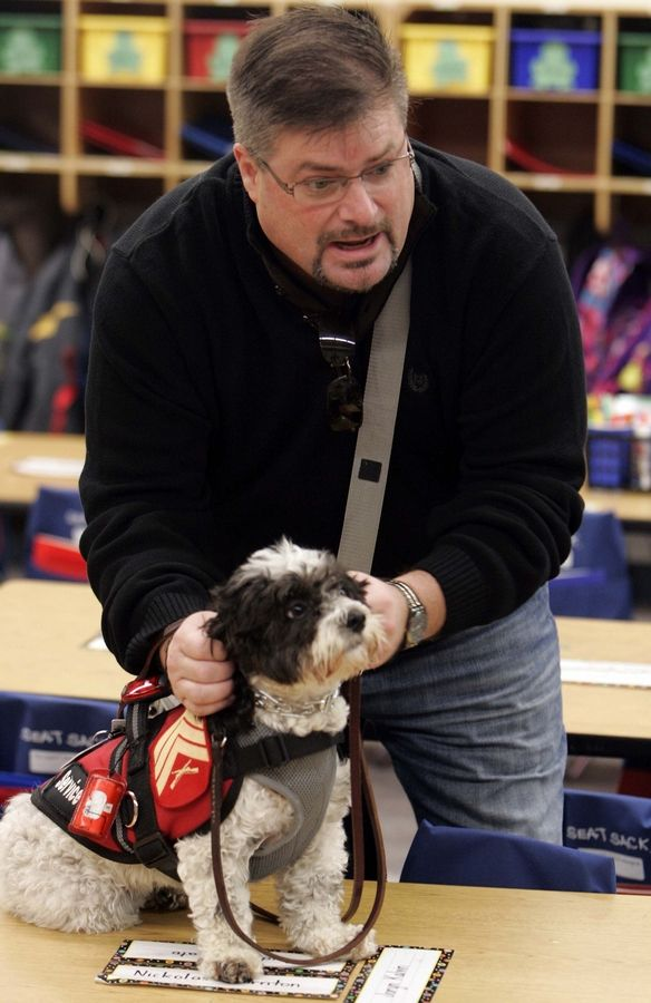 Dan Sauer of Hampshire answers questions about veterans from Caitlin Berry's kindergarten class at Hampshire Elementary School. Sauer, a former sergeant who served in the Marines during Desert Storm, suffers with PTSD. He never leaves the house without his service dog, Chloe, who helps calm him.