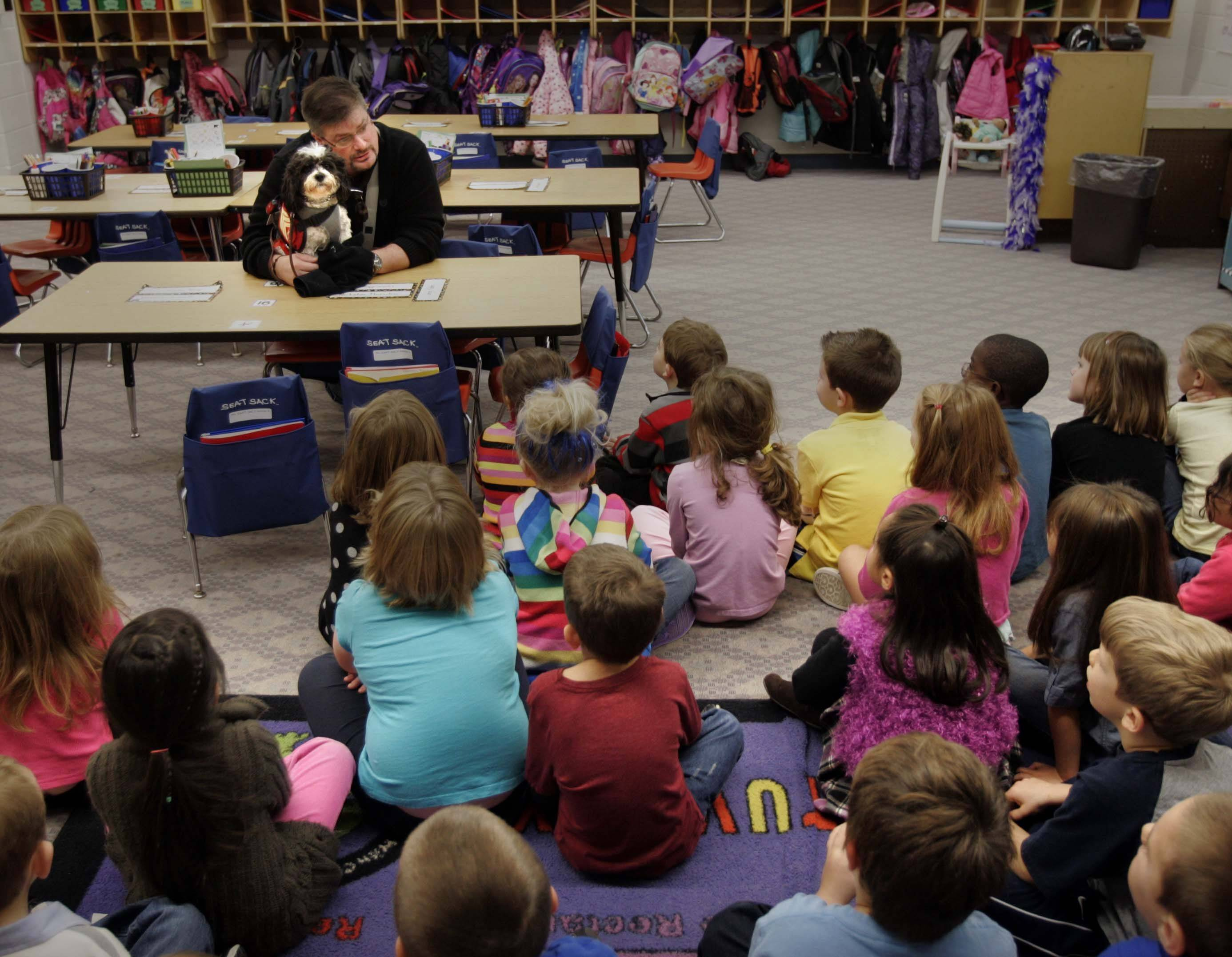 Dan Sauer of Gilberts talks to Caitlin Berry's kindergarten class at Hampshire Elementary School. Sauer, a former sergeant in the Marines, has been working with Chloe, a service dog that helps him deal with PTSD.
