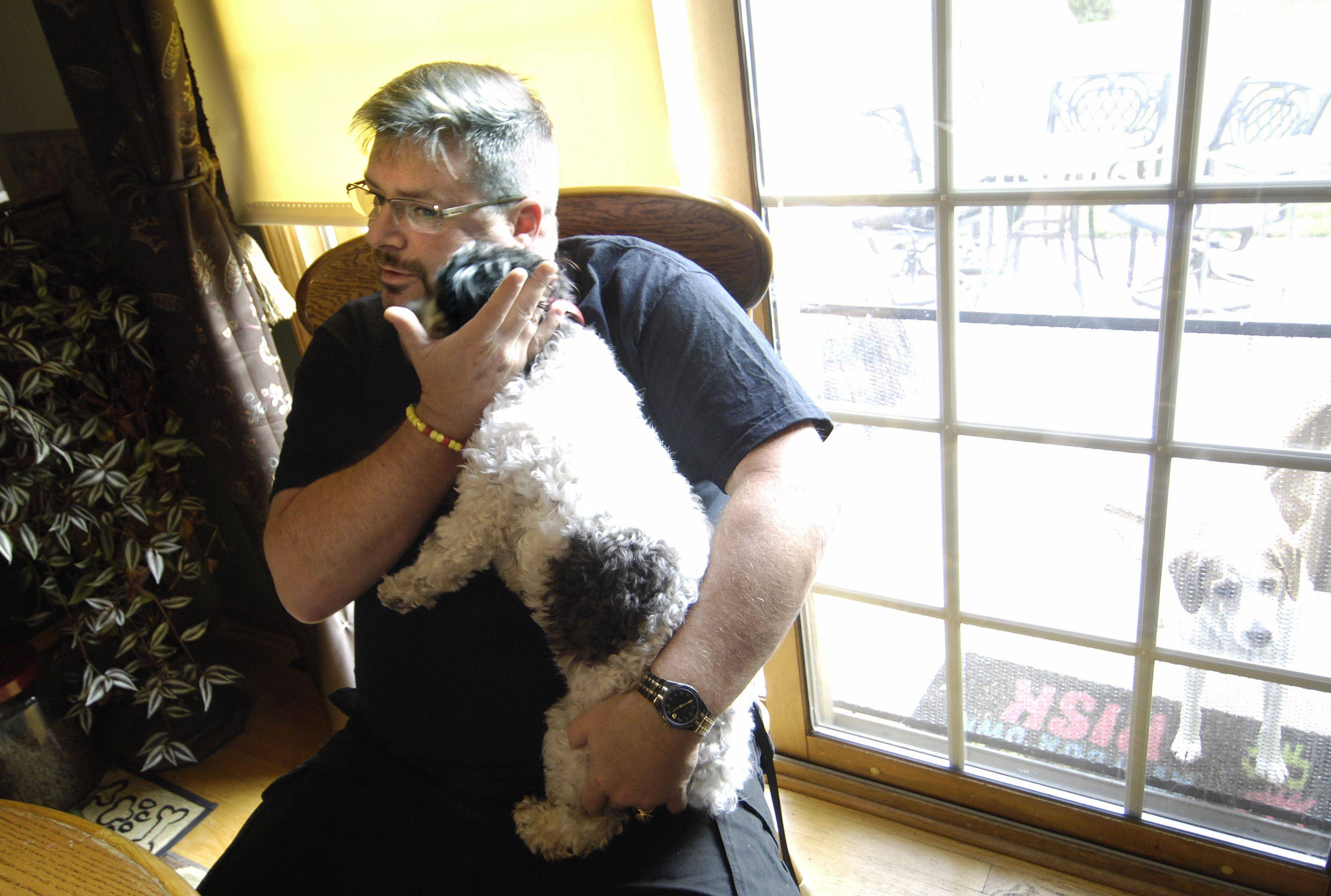 Dan Sauer, holds his service dog, Chloe, in his Hampshire home. Sauer is a Desert Storm veteran living with PTSD.