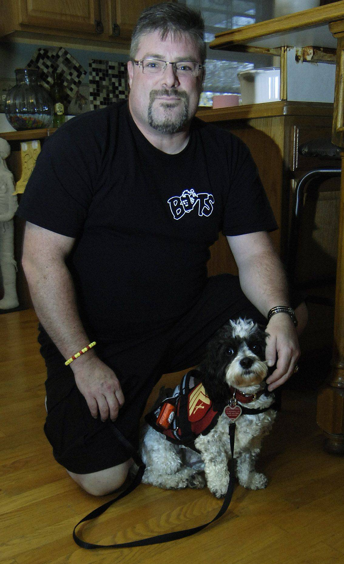 Dan Sauer poses with his service dog, Chloe, in his Hampshire home. He is a Desert Storm veteran and is living with PTSD.