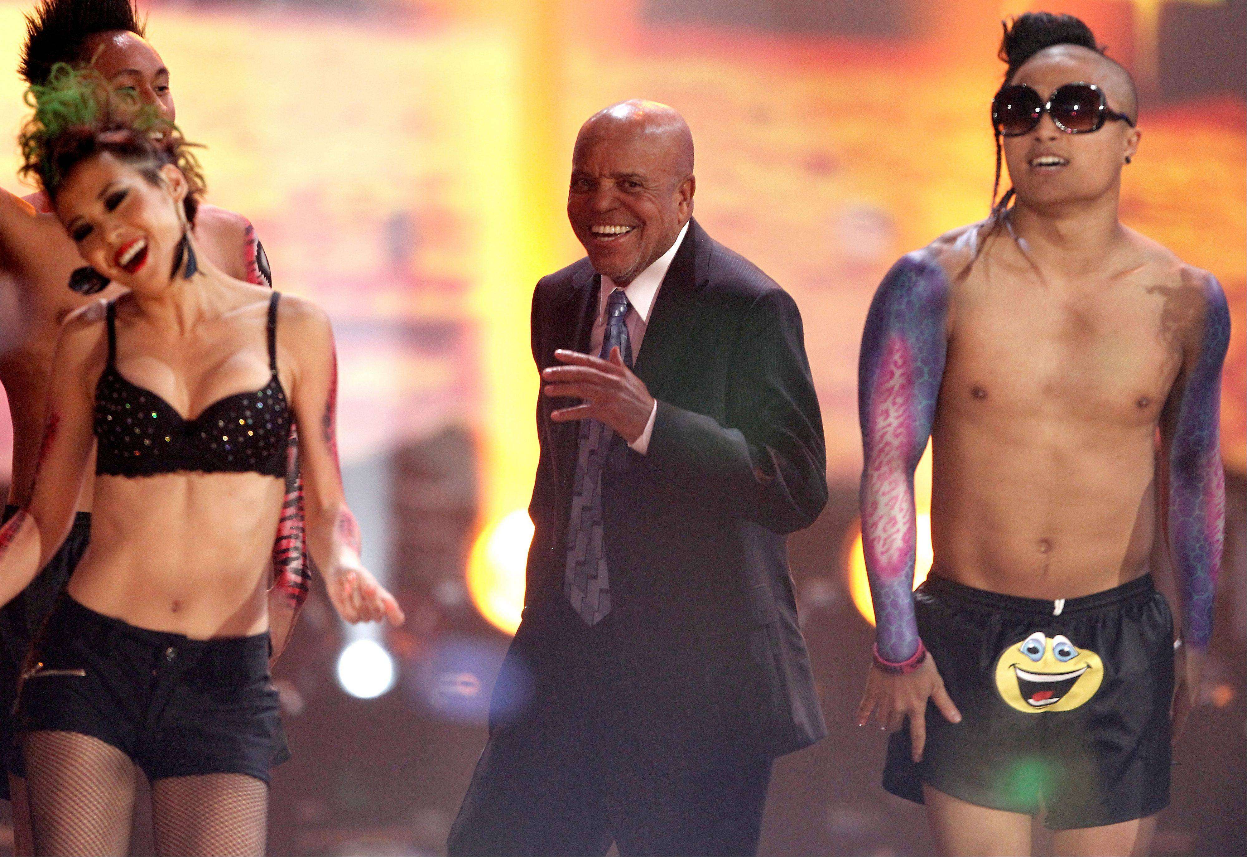 Berry Gordy, center, dances onstage while LMFAO performs at the 39th Annual American Music Awards on Sunday, Nov. 20, 2011 in Los Angeles.