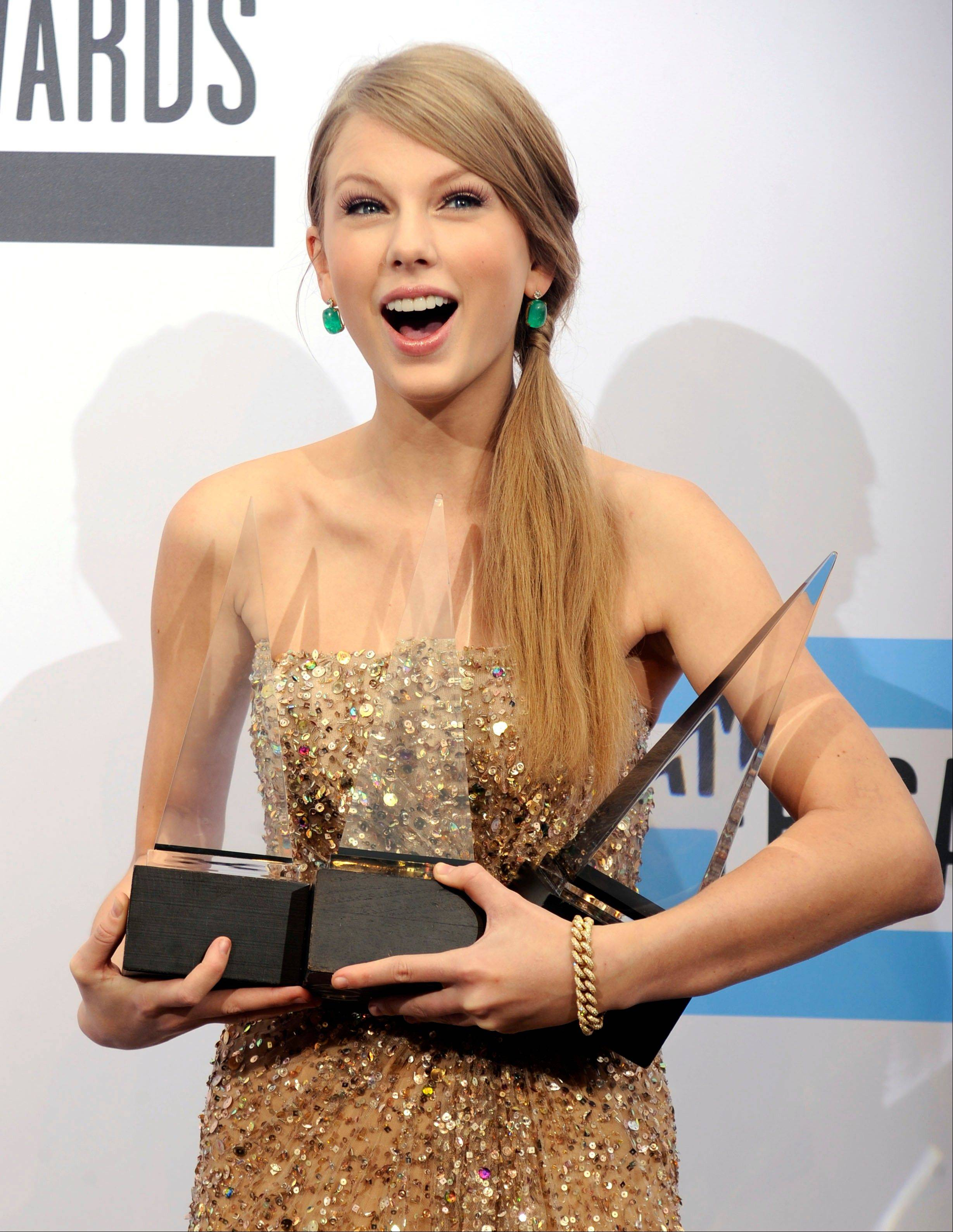 Taylor Swift poses backstage with the awards for country favorite female artist, country favorite album, and artist of the year at the 39th Annual American Music Awards on Sunday, Nov. 20, 2011 in Los Angeles. (AP Photo/Chris Pizzello)