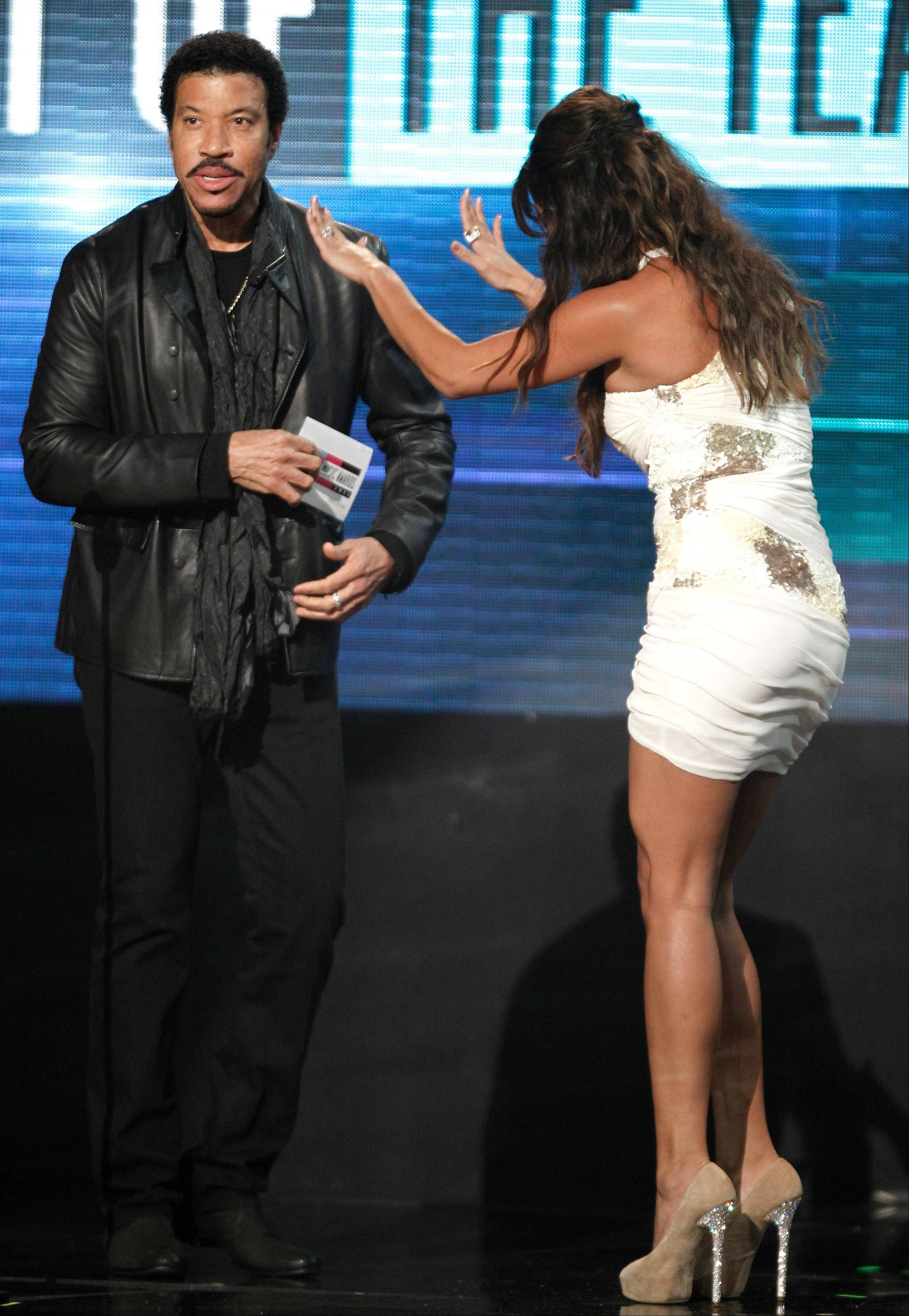 Lionel Richie, left, and Vanessa Minnillo present the award for artist of the year at the 39th Annual American Music Awards on Sunday, Nov. 20, 2011 in Los Angeles.