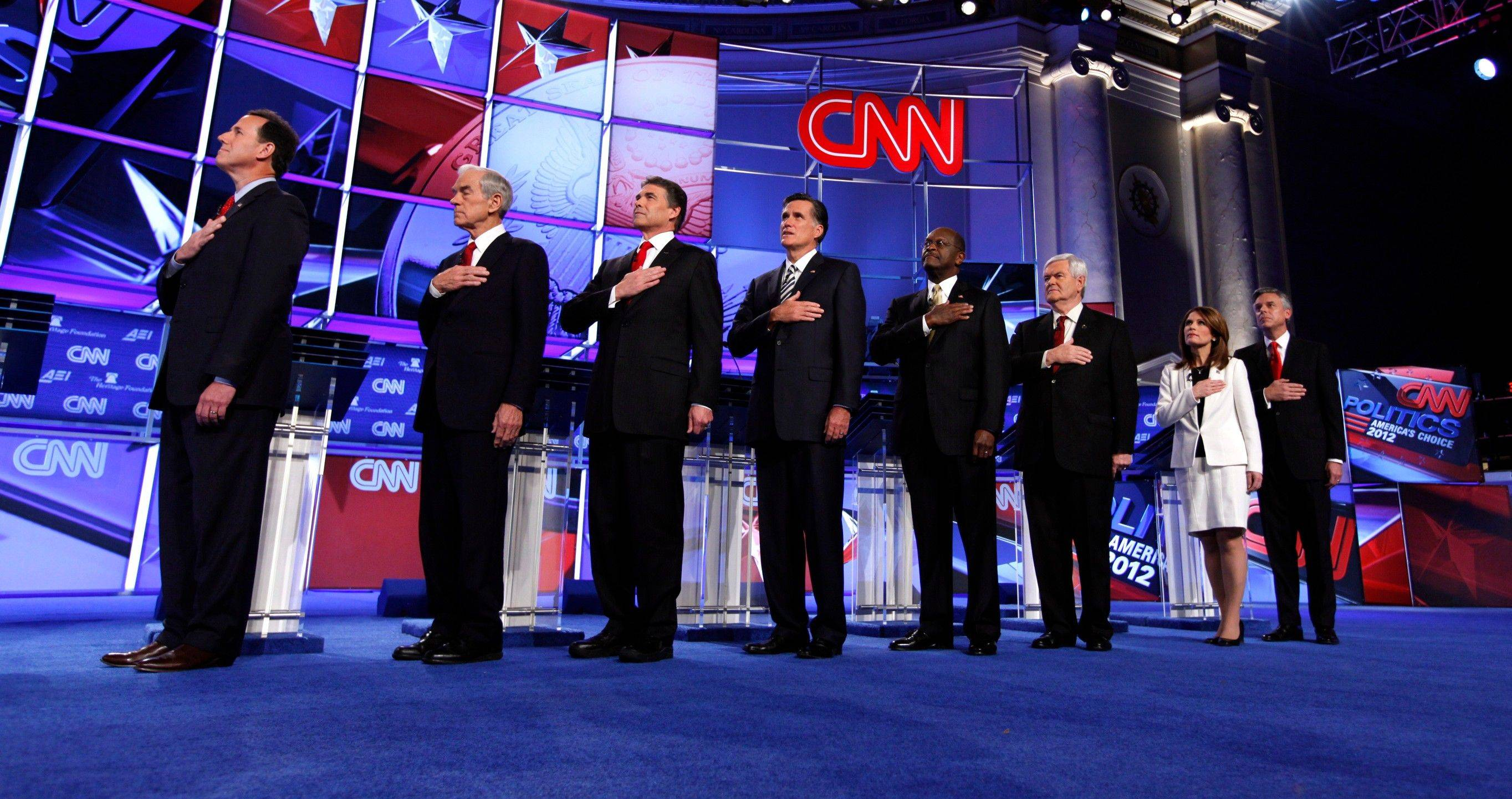 Republican presidential candidates from left, former Pennsylvania Sen. Rick Santorum, Rep. Ron Paul, R-Texas, Texas Gov. Rick Perry, former Massachusetts Gov. Mitt Romney, businessman Herman Cain, former House Speaker Newt Gingrich, Rep. Michele Bachmann, R-Minn., and former Utah Gov. Jon Huntsman stand for the National Anthem before a Republican presidential debate in Washington, Tuesday, Nov. 22, 2011.