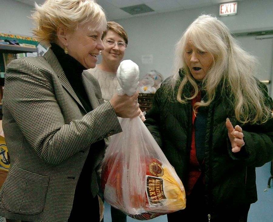 "Mary Insprucker of Catholic Charities, left, hands out their last turkey to Helga O'Malley of Niles at the organization's Des Plaines food pantry. Asked if she was planning to make a Thanksgiving dinner, O'Malley replied, ""I am now!"""