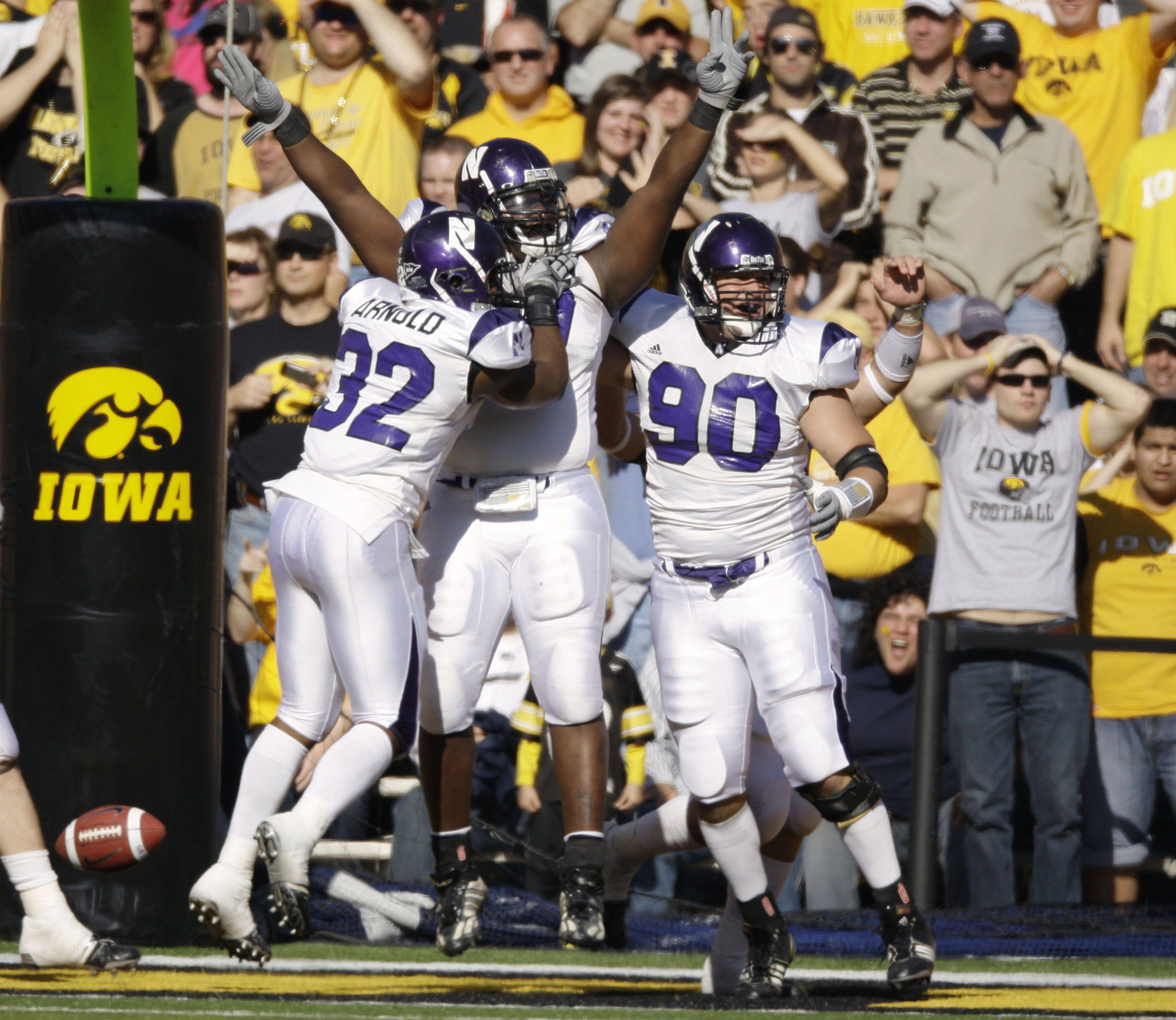 Northwestern's Marshall Thomas, center, celebrates with teammates David Arnold, left, and Jack DiNardo, right, after he recovered an Iowa fumble for a touchdown against Iowa in 2009.