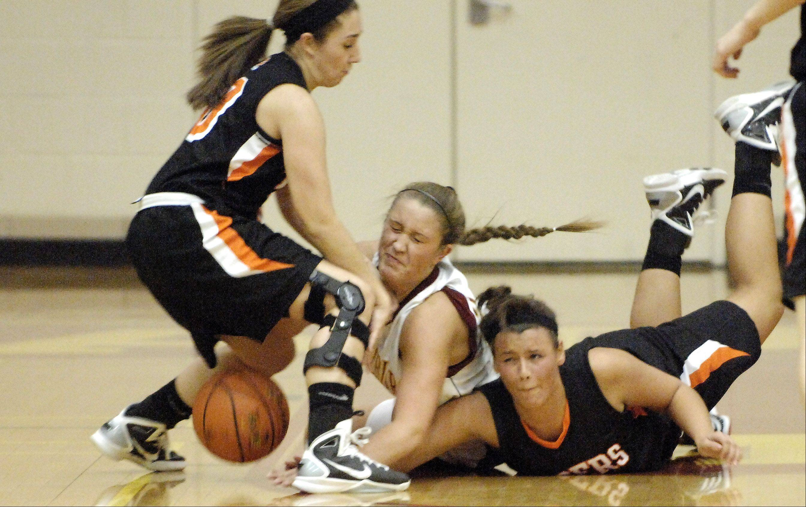 Wheaton Warrenville South's Sierra Bisso, right, and Krysta Watts, left, battle Schaumburg's Alyssa Saklak for a loose ball during Thursday's game at the Schaumburg Thanksgiving tournament.