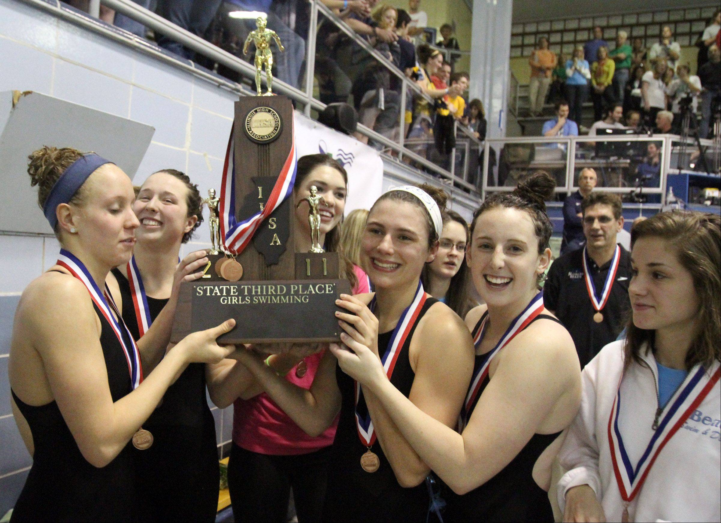 Rosary celebrates with the third place team trophy at the IHSA state swimming championships in Winnetka on Saturday.