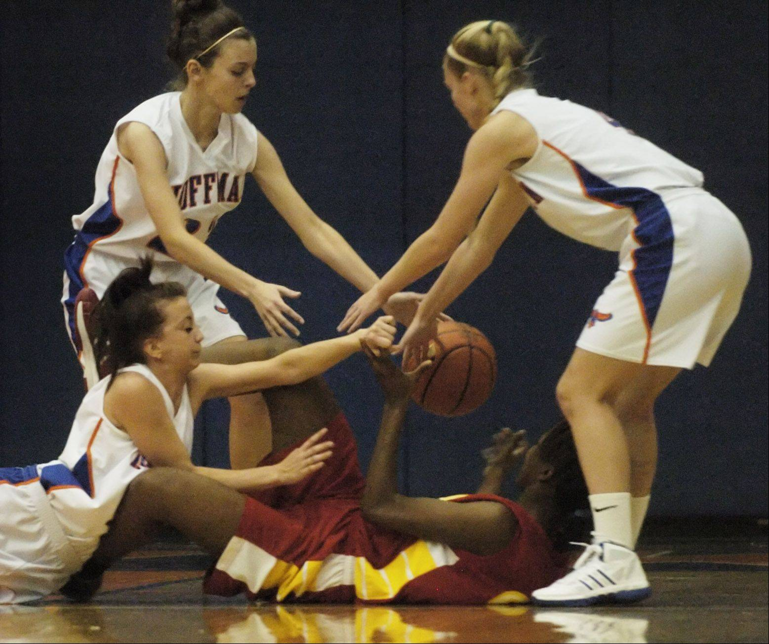 Hoffman Estates players from left Sara Burns, Rachel Mirabile and Mary Pettit strip the ball from North Lawndale's Caprisha Treaduell during Tuesday's game in Hoffman Estates.