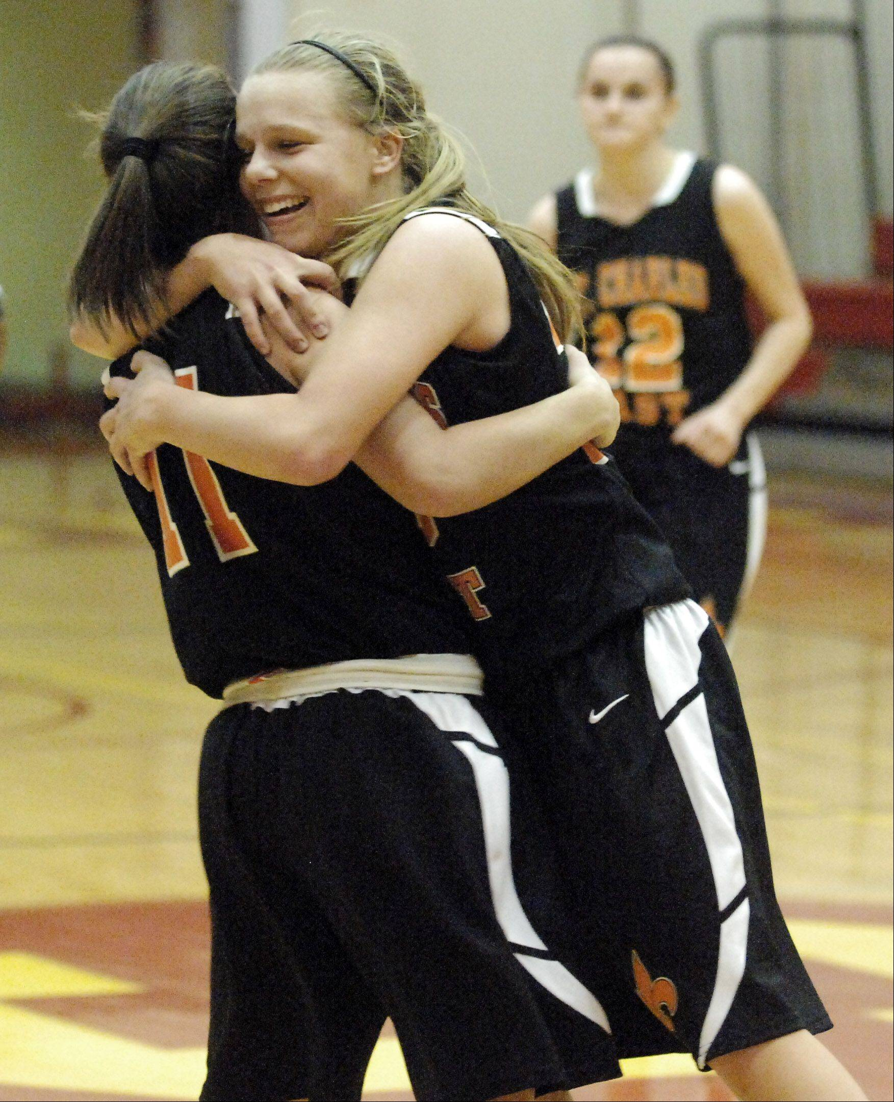 St. Charles East teammates Amanda Hilton, right, and Carly Pottie hug after their comeback win over Proviso West during Thursday's game at the Schaumburg Thanksgiving tournament.