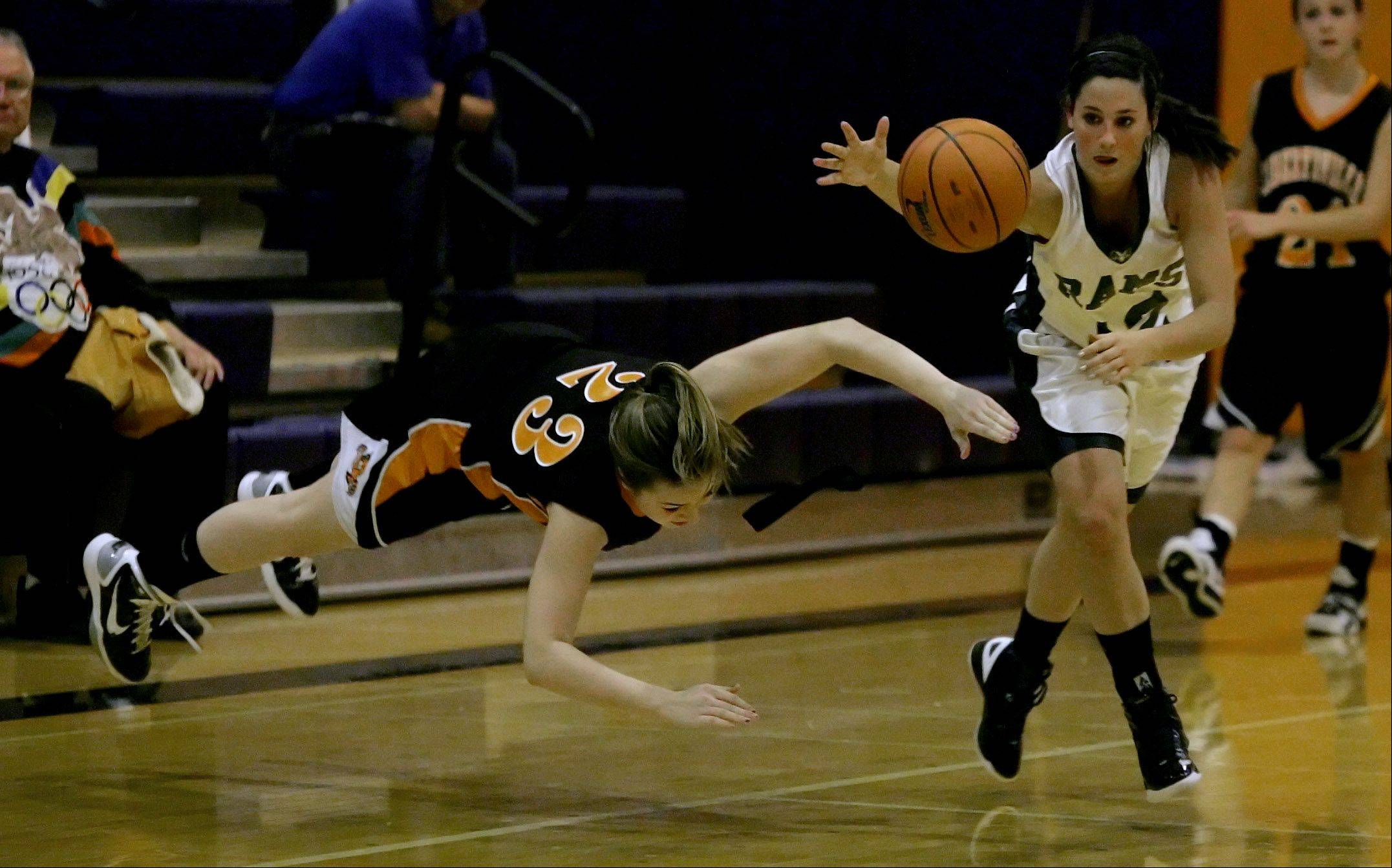 Libertyville Molly Moon, left, and Grayslake Central's Claire Brennan dive for a loose ball during Thursday's game at the Bison Classic Girls Varsity Basketball Thanksgiving Tournament in Buffalo Grove.