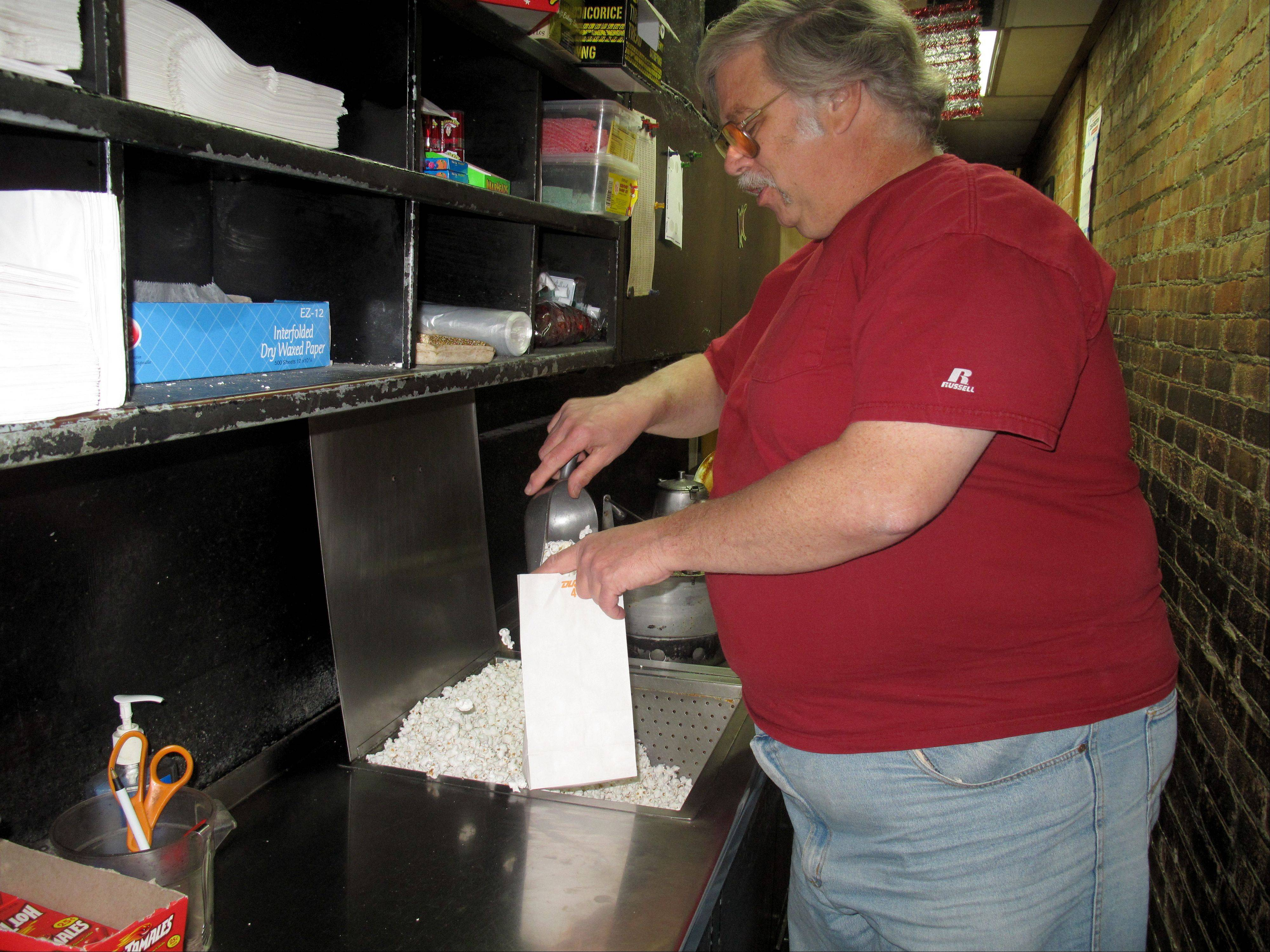 Bill Wakefield fills a small bag of popcorn for a customer. Wakefield estimates that he goes through 8 tons of popcorn kernels per year.