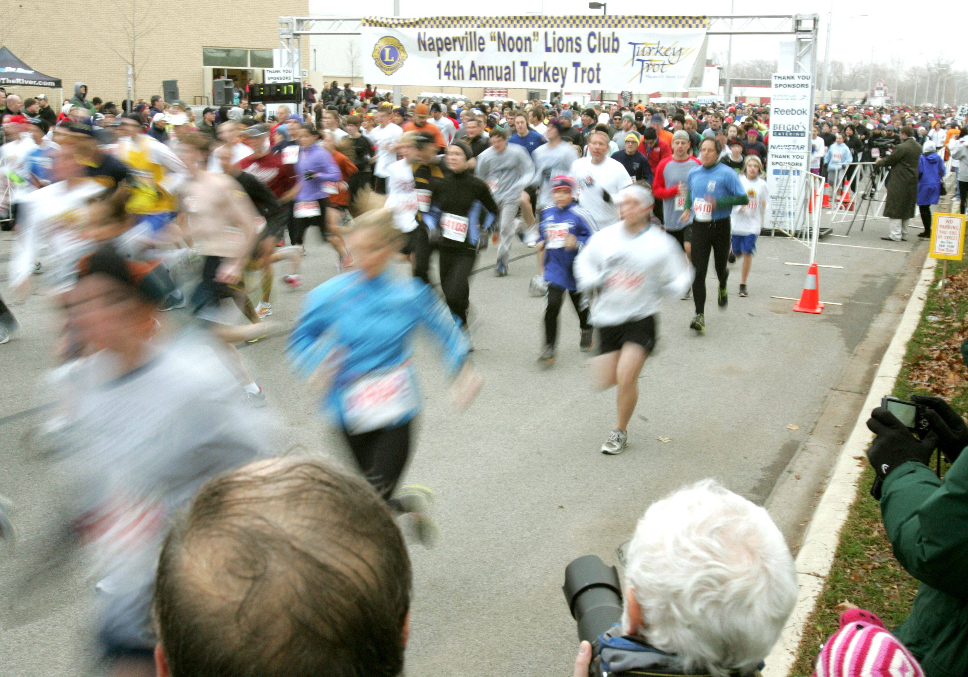 Runners funnel through the starting gate Thursday at the Naperville Turkey Trot.