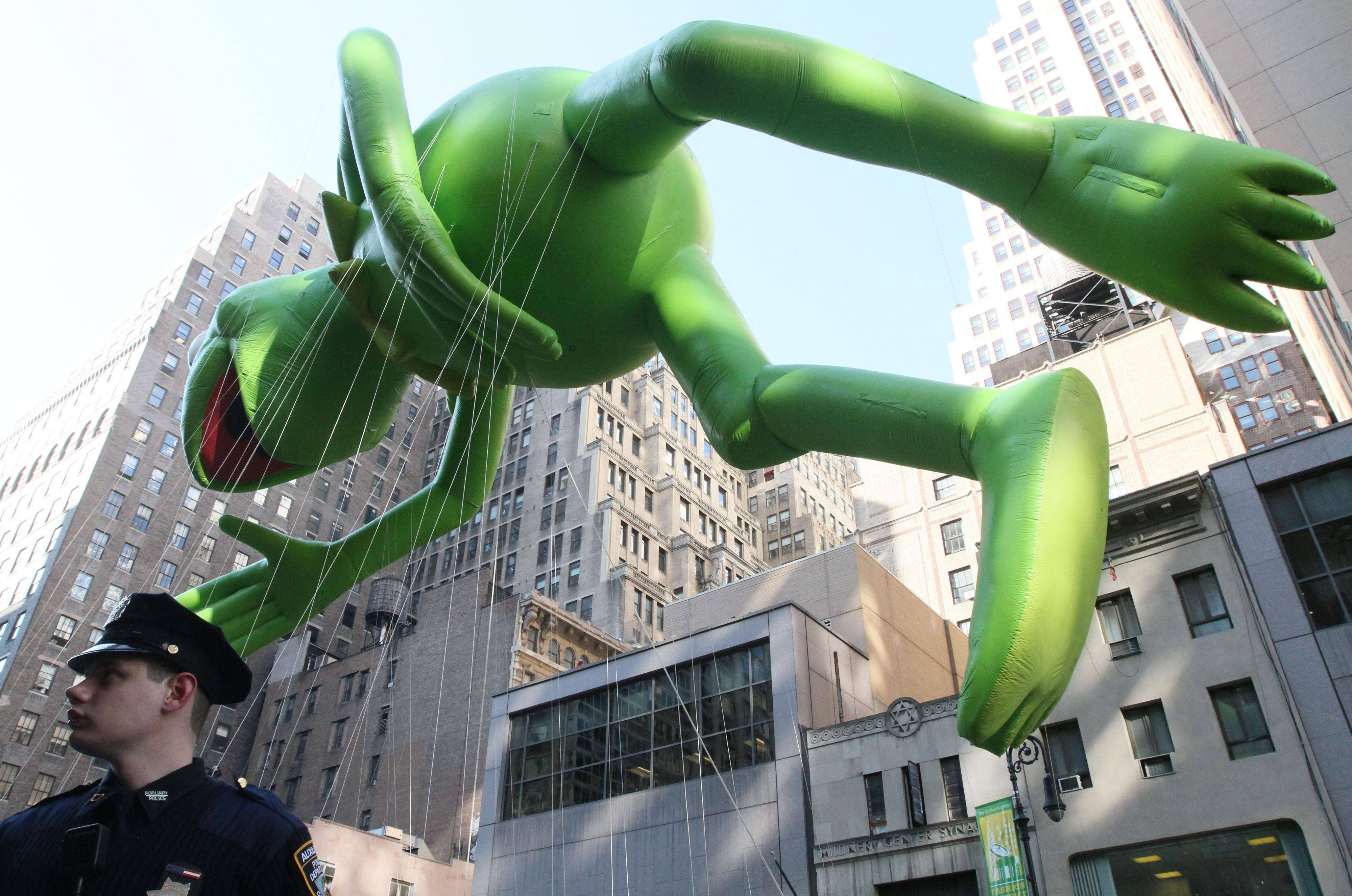 Christopher Poll, a member of the New York City Police Department Auxiliary Police, keeps watch as the Kermit the Frog balloon makes its way down New York's Sixth Avenue during the 85th Annual Macy's Thanksgiving Day Parade Thursday Nov. 24, 2011.