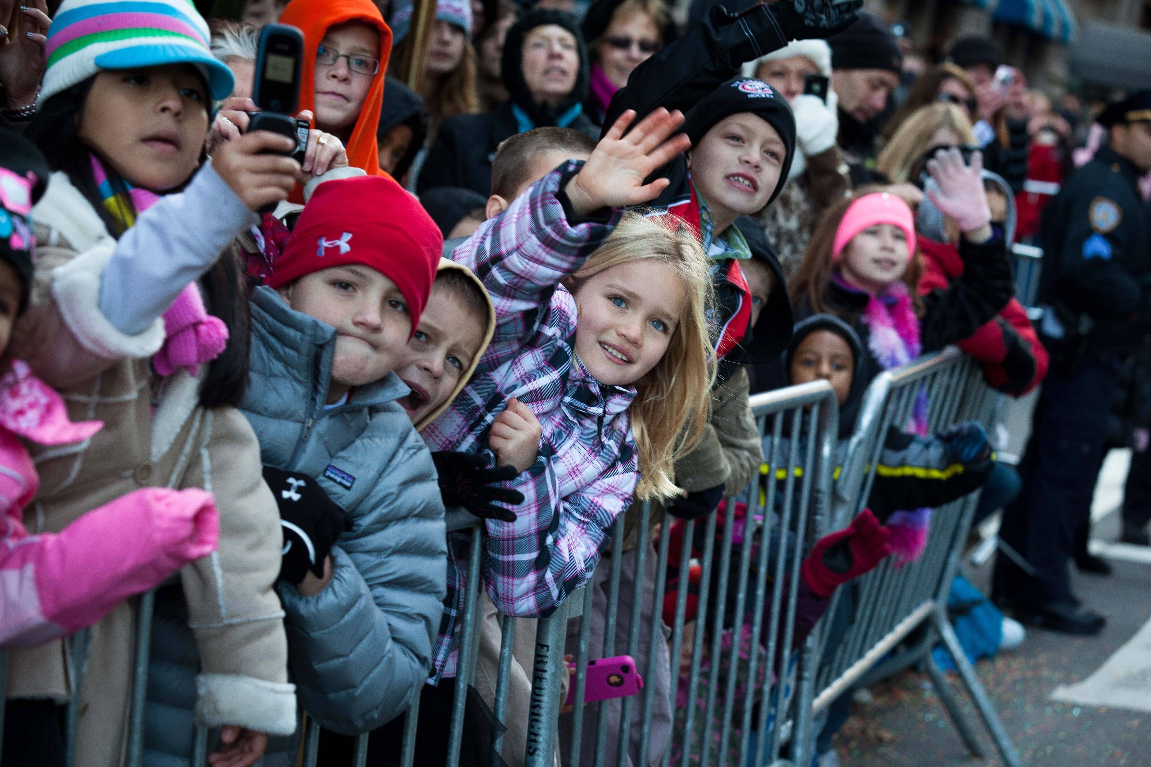 Young spectators wave to Santa Claus as he rolls down 7th Avenue during the Macy's Thanksgiving Day Parade, Thursday, Nov. 24, 2011, in New York. A jetpack-wearing monkey and a freakish creation from filmmaker Tim Burton are two of the big new balloons that will make their inaugural appearances in front of millions of people at this year's parade.