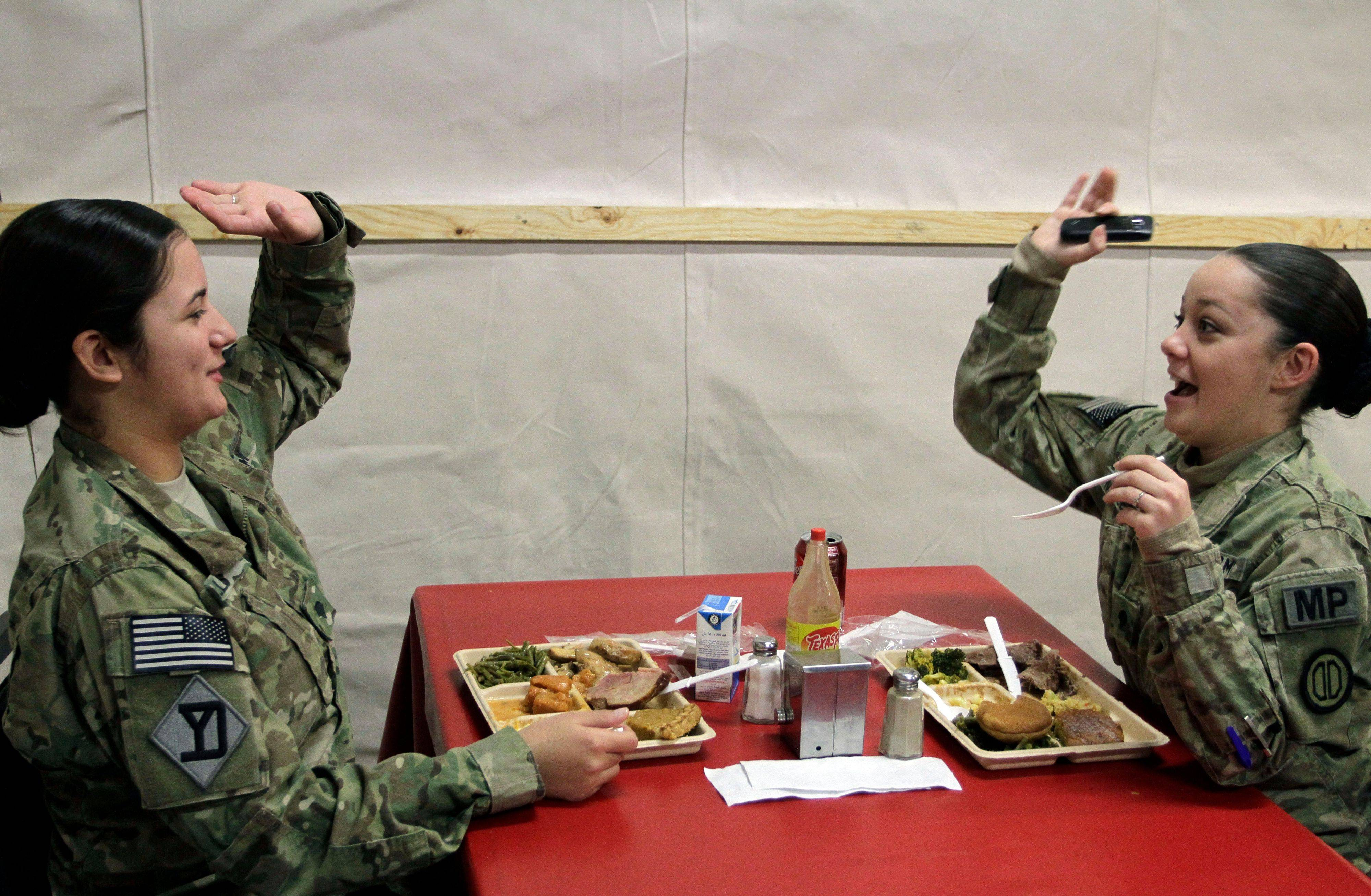 U.S. soldiers react, as they eat lunch meal to mark Thanksgiving Day at the U.S. base Camp Eggers in Kabul, Afghanistan, Thursday, Nov. 24, 2011.