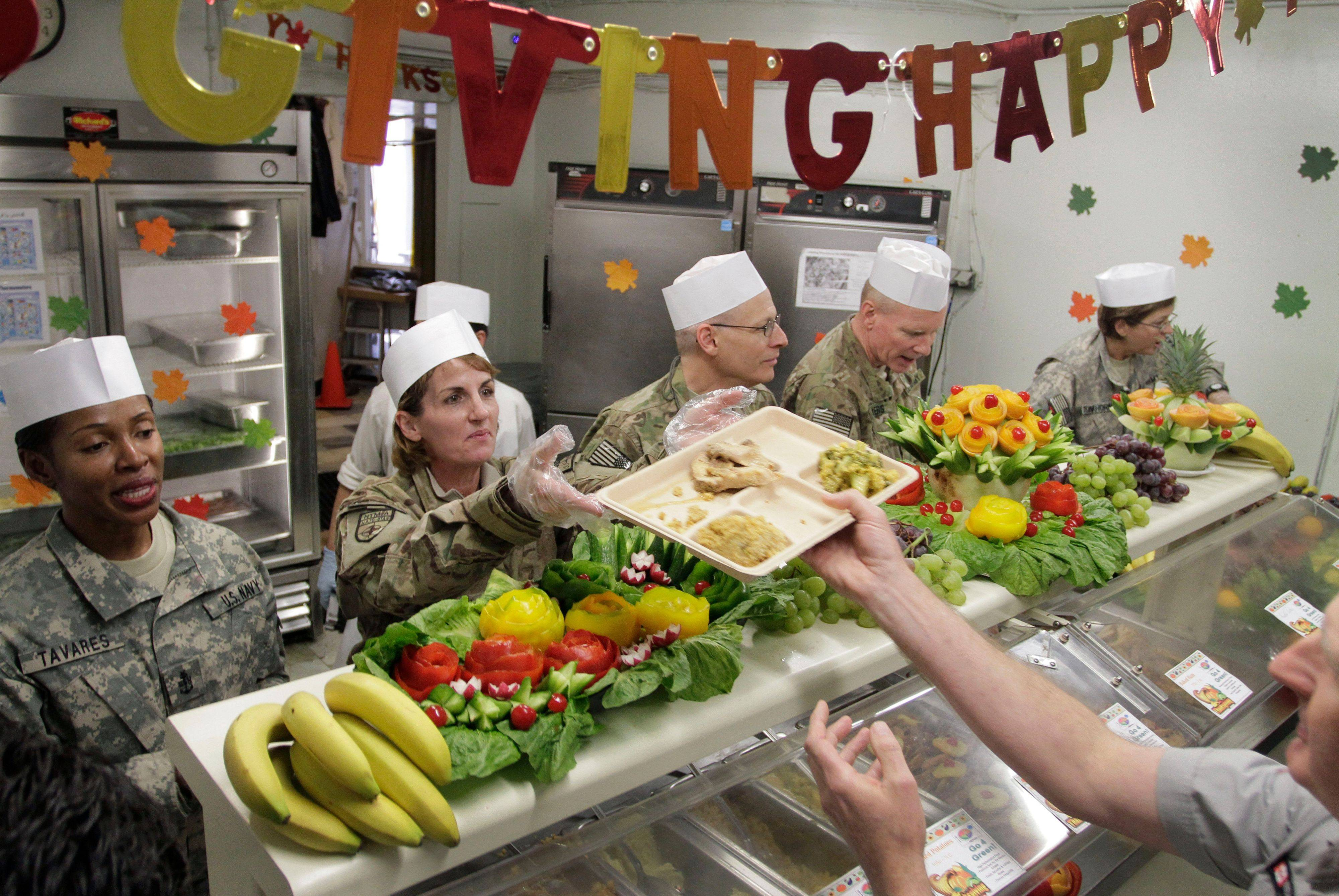 U.S. soldiers, left, distribute meals to comrades to mark Thanksgiving Day at the U.S. base Camp Eggers in Kabul, Afghanistan, Thursday, Nov. 24, 2011.