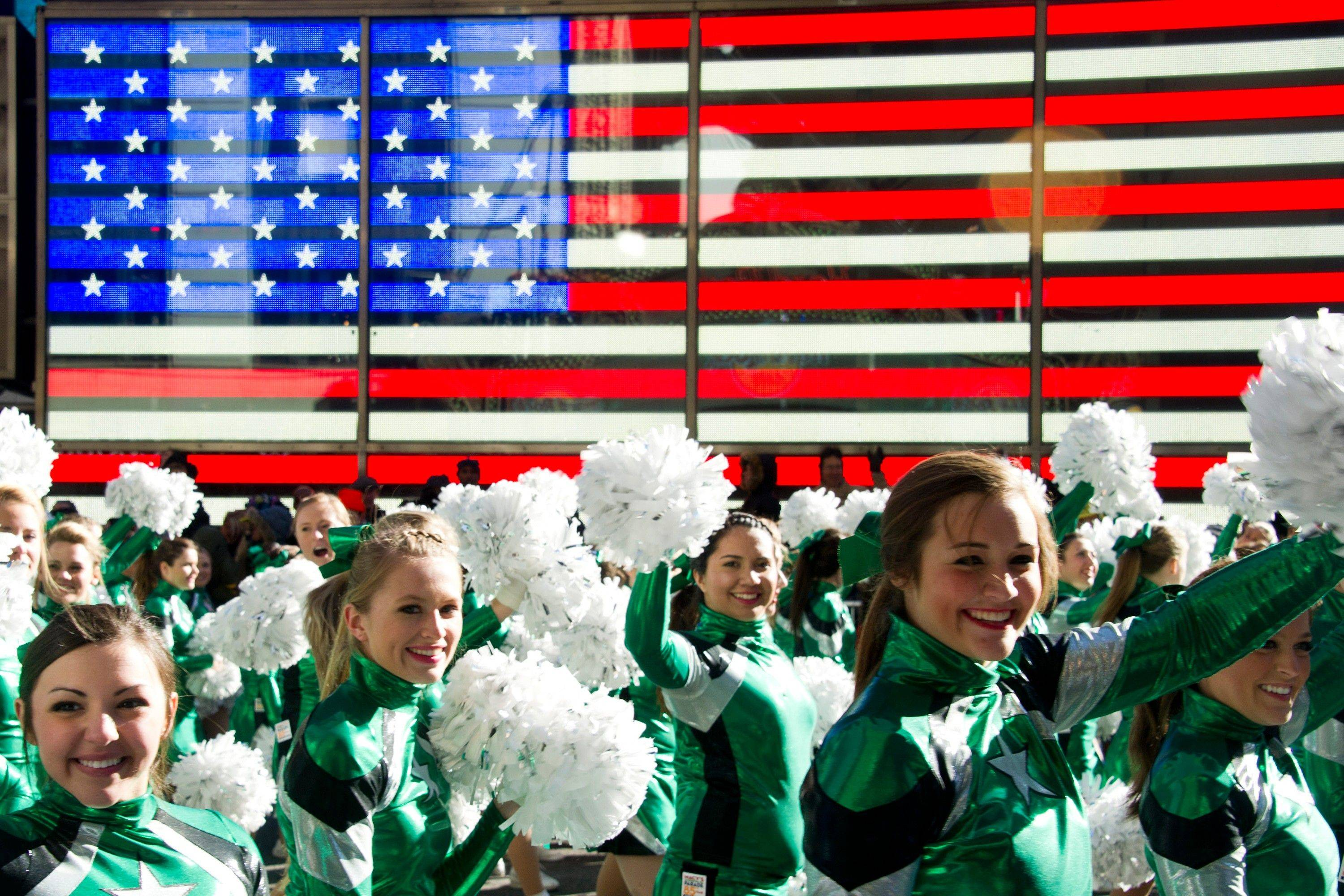 Cheerleaders march through Times Square in the Macy's Thanksgiving Day Parade in New York, Thursday, Nov. 24, 2011. A jetpack-wearing monkey and a freakish creation from filmmaker Tim Burton are two of the big new balloons that will make their inaugural appearances in front of millions of people at this year's parade.