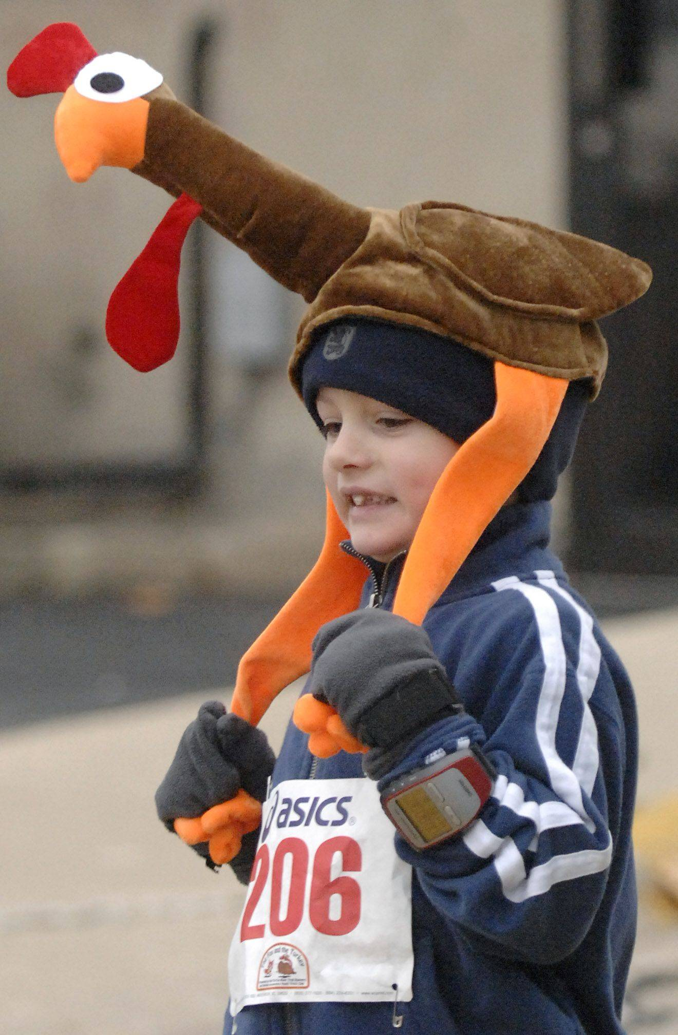 Lucas Rohan, 6, of Batavia hangs on tight to the legs of his turkey hat as he nears the finish line for the 15th annual Fox and the Turkey Youth Mile run in Batavia on Thanksgiving morning.