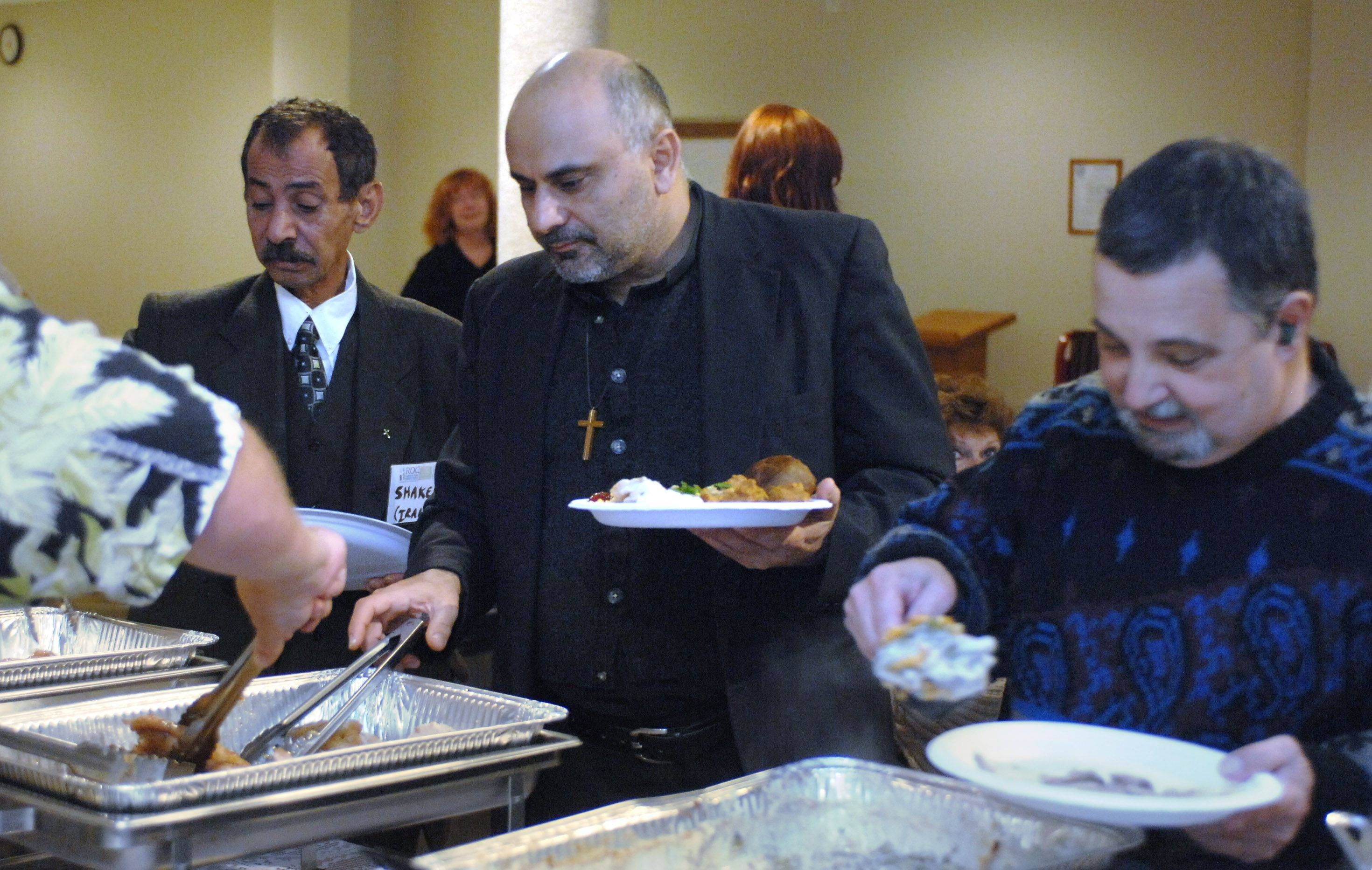 St. Matthew Lutheran Church in Hawthorn Woods held their Thanksgiving meal Thursday with guests, from left, Shaker Khamissi of Iran, Pastor Hicham Chehab of Salam Arabic Fellowship Church and Tony Crisara of Mundelein.