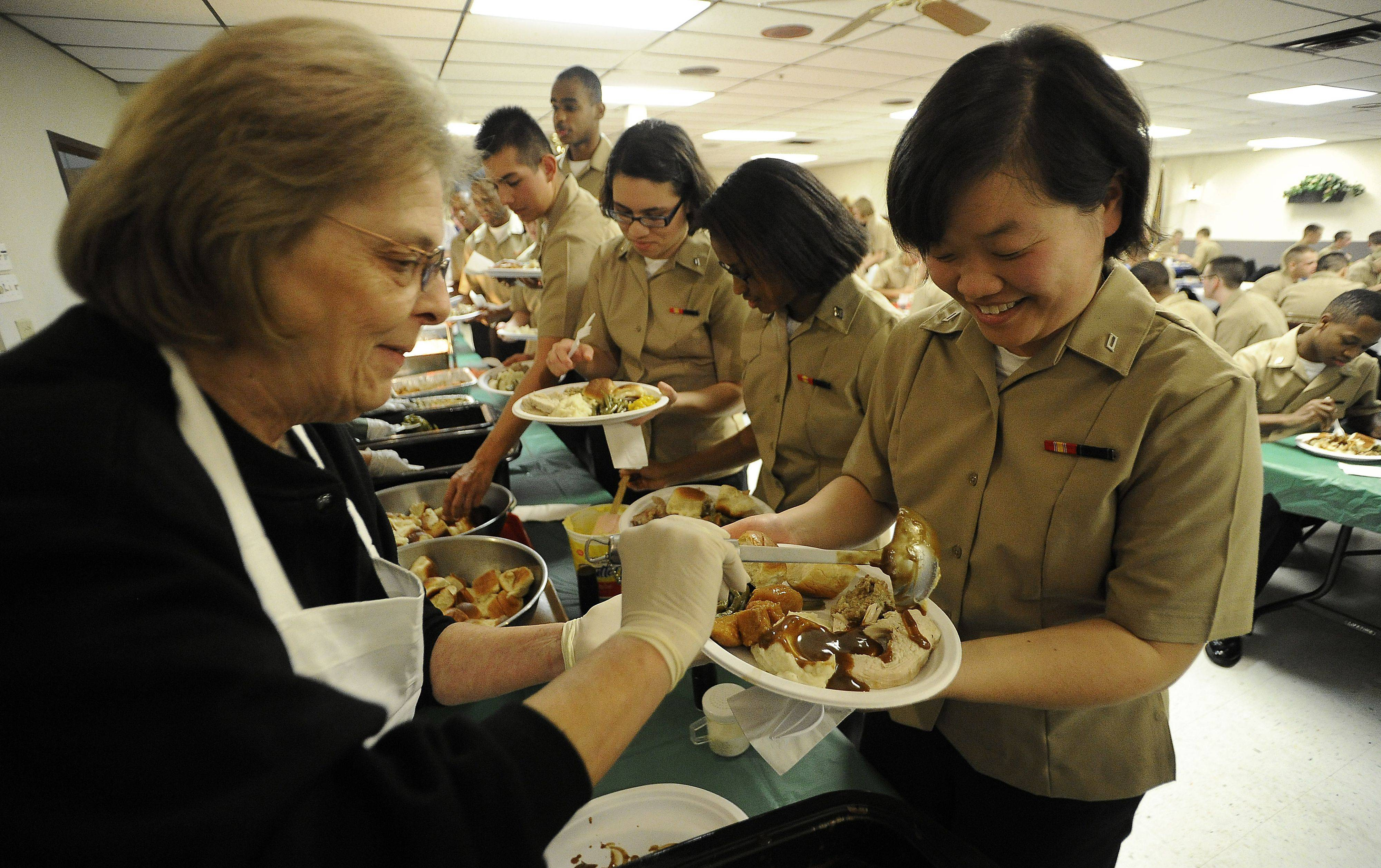 Darlene Dorsey of Wheeling carefully spreads gravy over the Thanksgiving turkey dinner of Sang Tian,24, of California at Wheeling Amvets on Thursday.