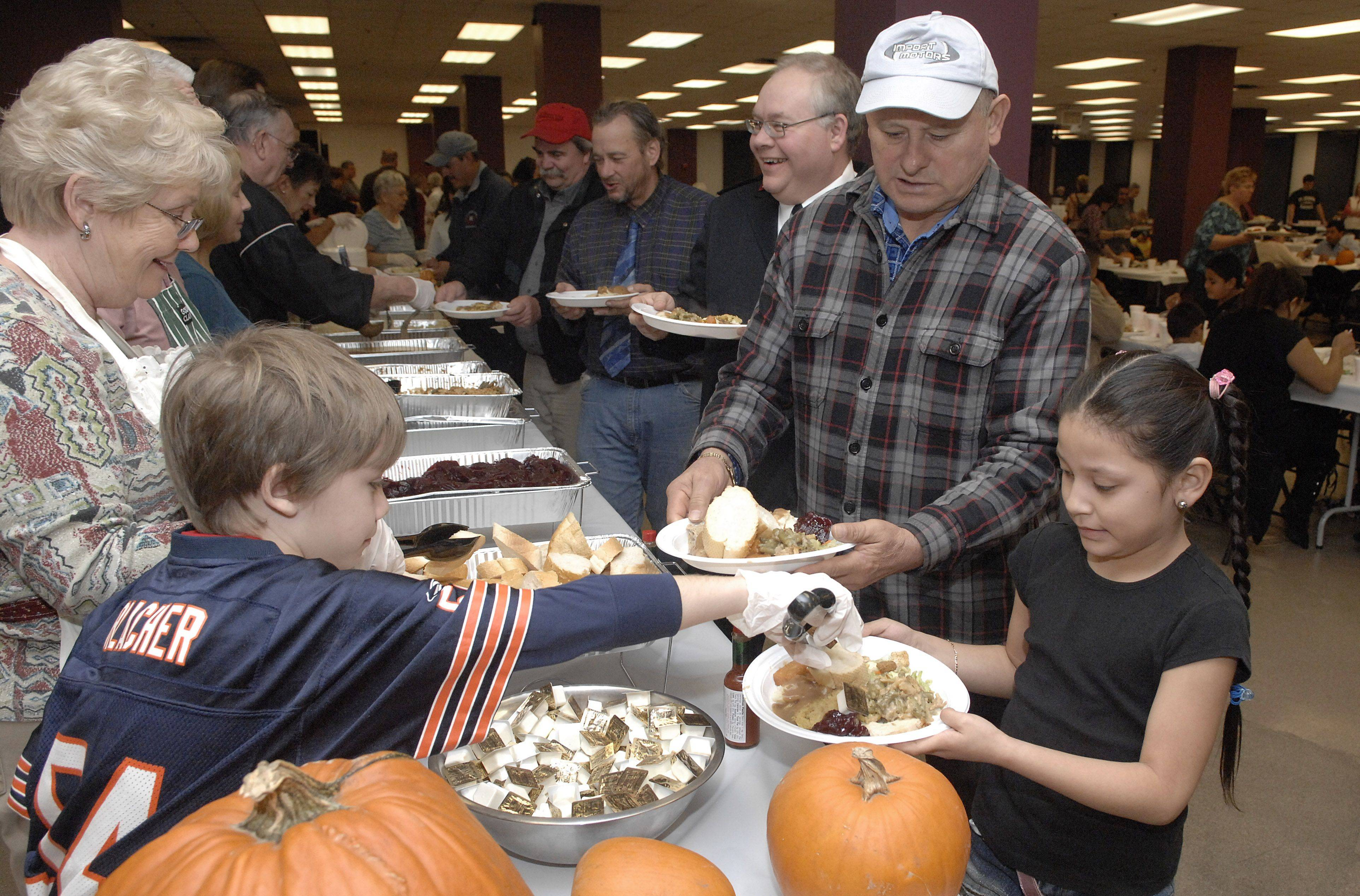 Mika Bradburn ,left, 9, of Downers Grove serves butter to Brianna Fernandez-Diaz ,right, 6, and her father, Ubaldo, of Elgin at the Thanksgiving Community Dinner at the Hemmens Cultural Center in Elgin. Mika was volunteering with his grandparents Ruth and John Bradburn of Elgin.