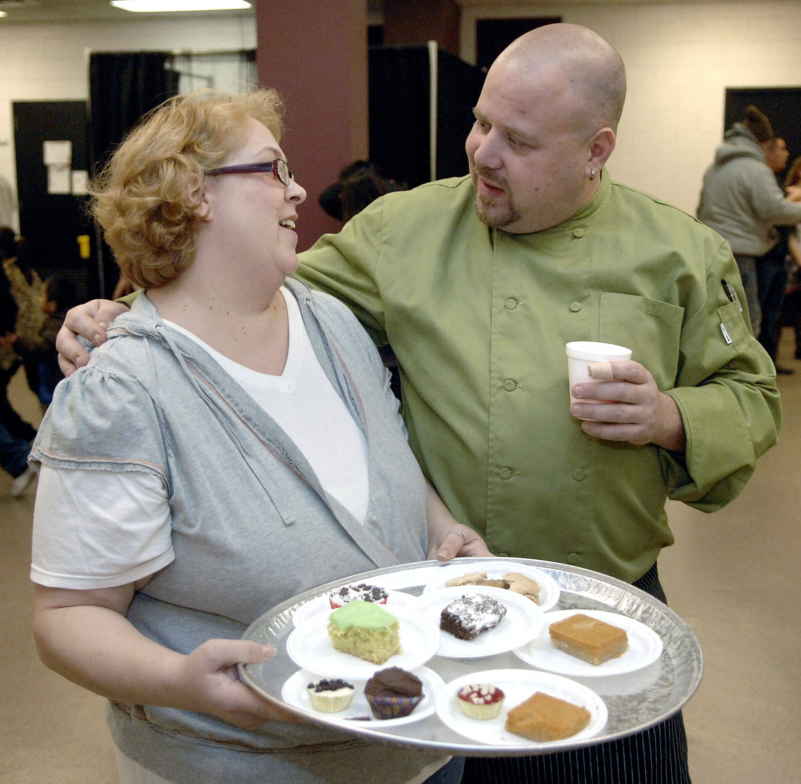 "Volunteer Angela Kibbe of Elgin greets Thanksgiving dinner organizer and chef Jeff Turner of ""In the Neighborhood Deli"" while serving desserts at the Hemmens Cultural Center. Kibbe is a brand new mother after trying for 12 years. She says she was so thankful that when she saw the ad in a newspaper asking for volunteers for the Thanksgiving dinner, she knew it was what she wanted to do this year."