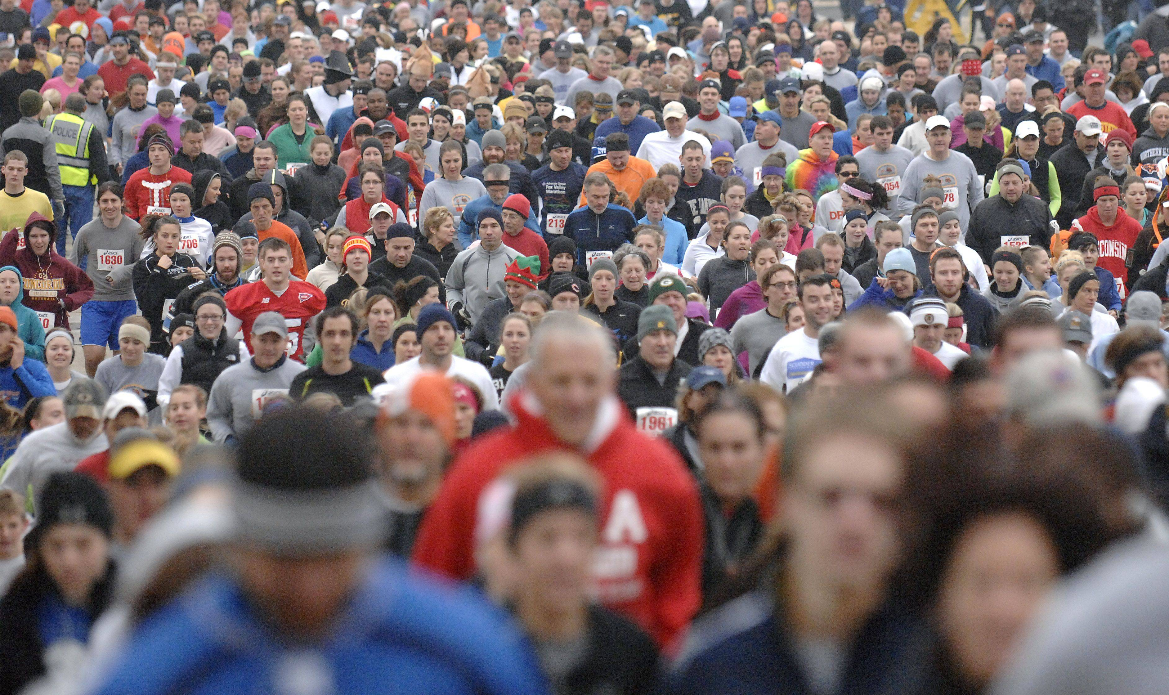 Hundreds take off for the start of the 15th annual Fox and the Turkey four-mile run in Batavia on Thanksgiving morning.