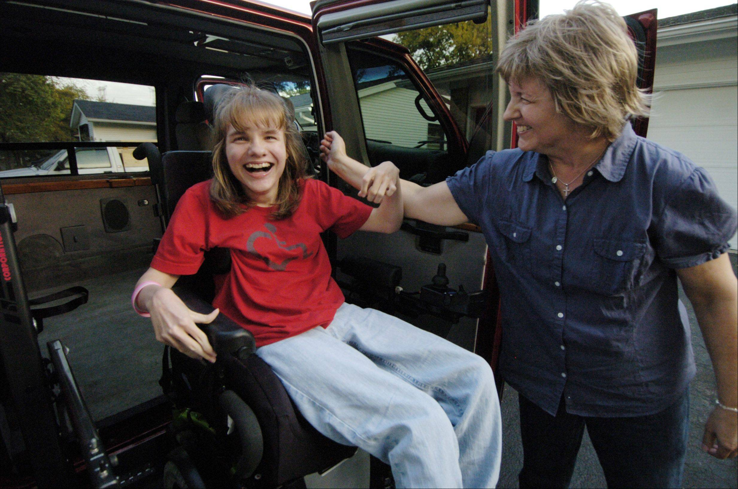 Meredith Evans smiles as her mom, Joan helps guide her into their family's new handicapped-accessible van, which was donated by Chris and Gail Margarites of Hawthorn Woods.