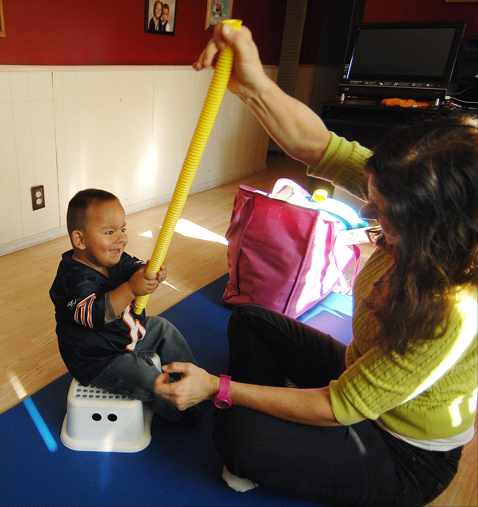 Nathan Saavedra works with Physical Therapist Sue Schmidt in his Carpentersville home Monday. Although the 3-year-old Carpentersville boy needs another kidney after the last donation failed, his family is grateful.