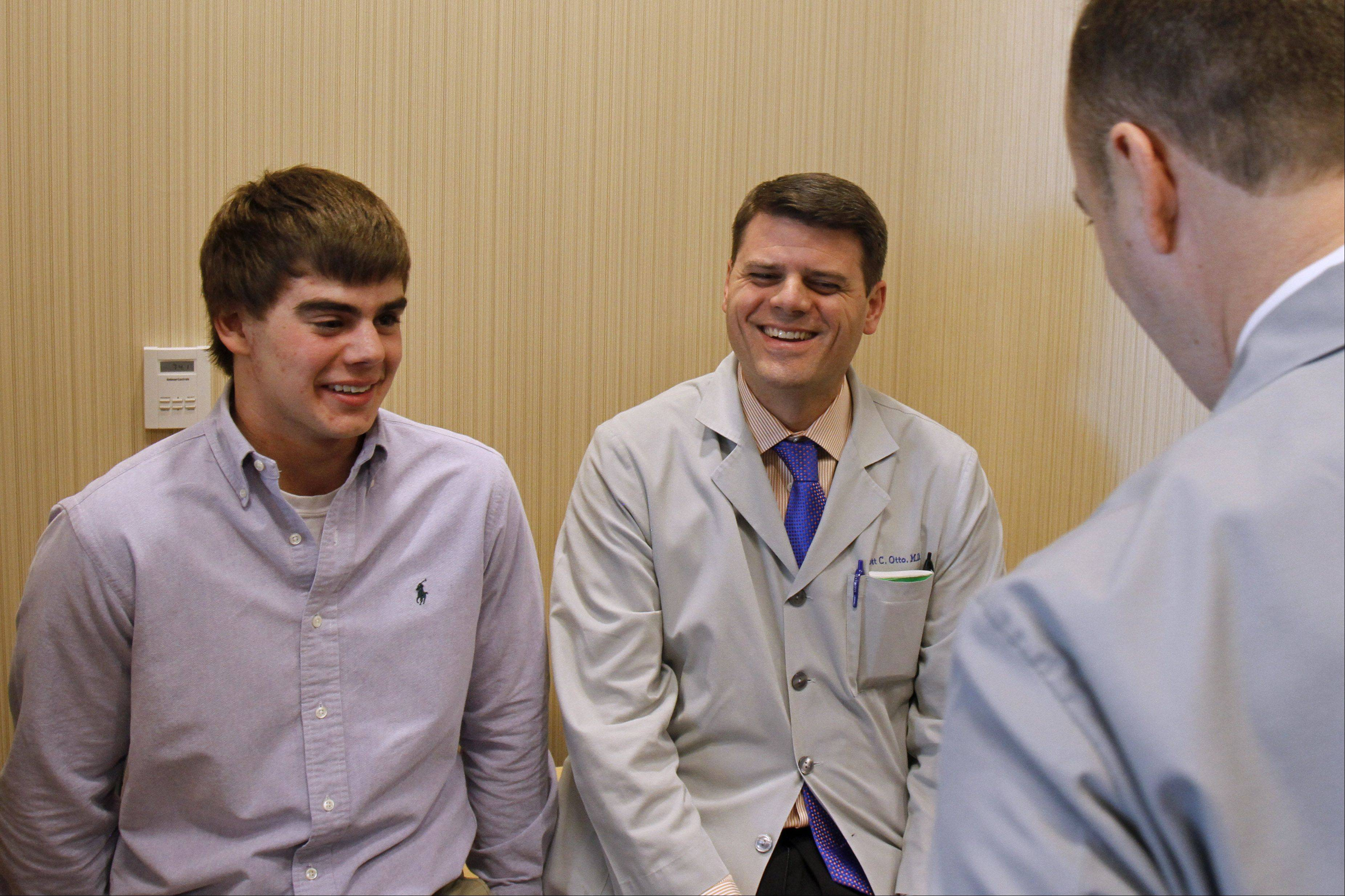 Forrest Ericksen of Lake Villa, left, laughs with surgeons Dr. Scott Otto, middle, and Dr. William Watson at Advocate Condell Medical Center in Libertyville Wednesday. The surgeons were on hand at Condell's level 1 trauma unit saved the 18-year-old's life after a snowmobile accident in 2010.