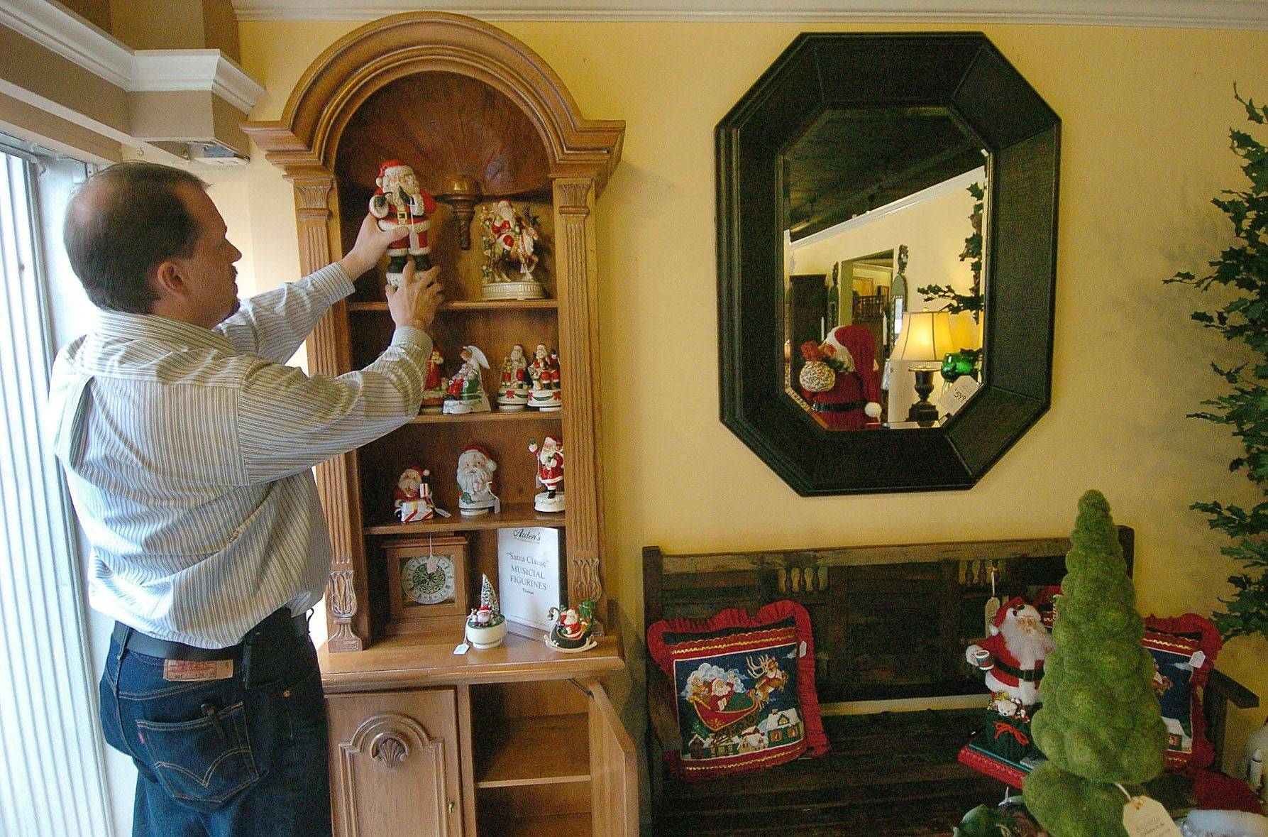 Co-owner Mike Main sets up Christmas decorations in the window display at Arden's furniture in downtown Libertyville.