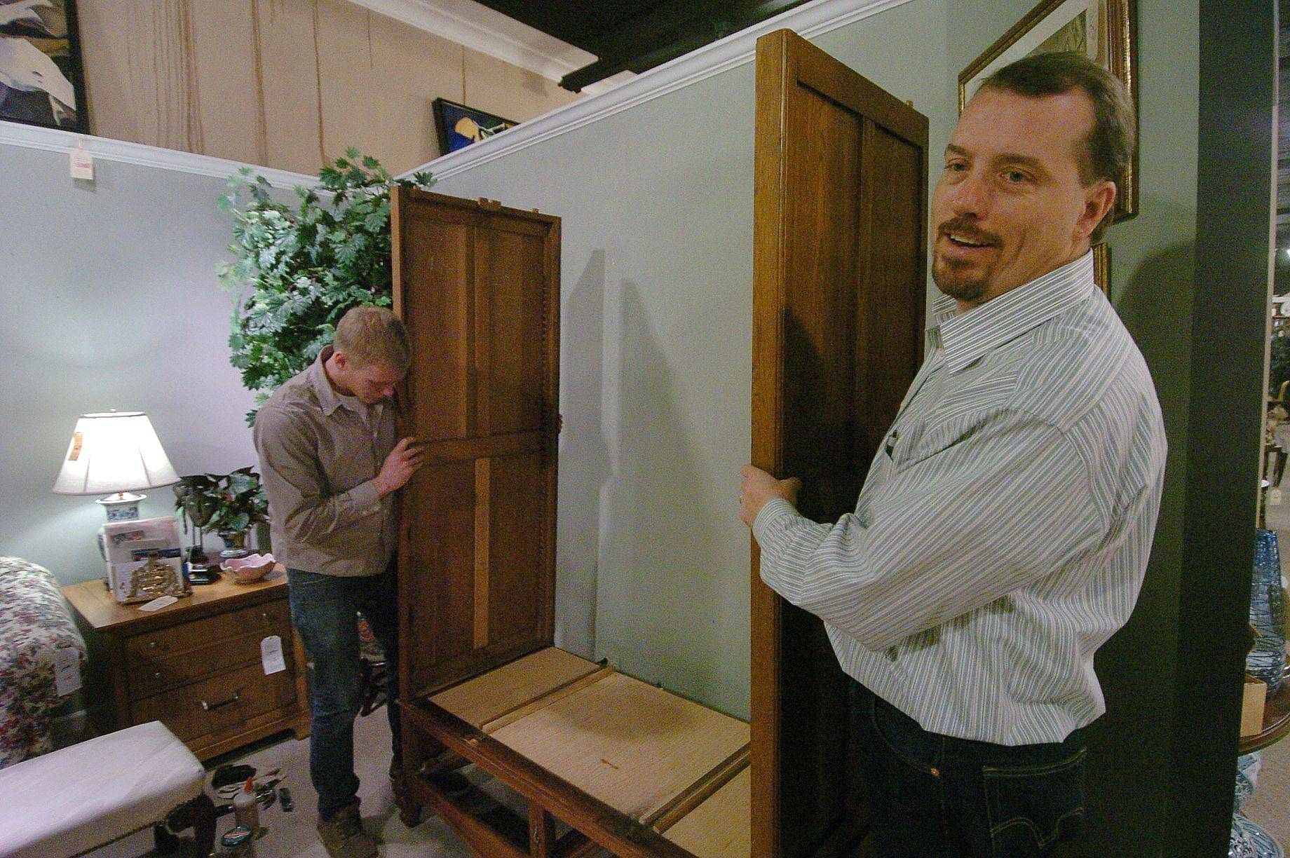 Co-owner Mike Main, right, and Alex Jensen assemble an armoire from the 1800s as a liquidation sale continues at Arden's furniture store in downtown Libertyville.