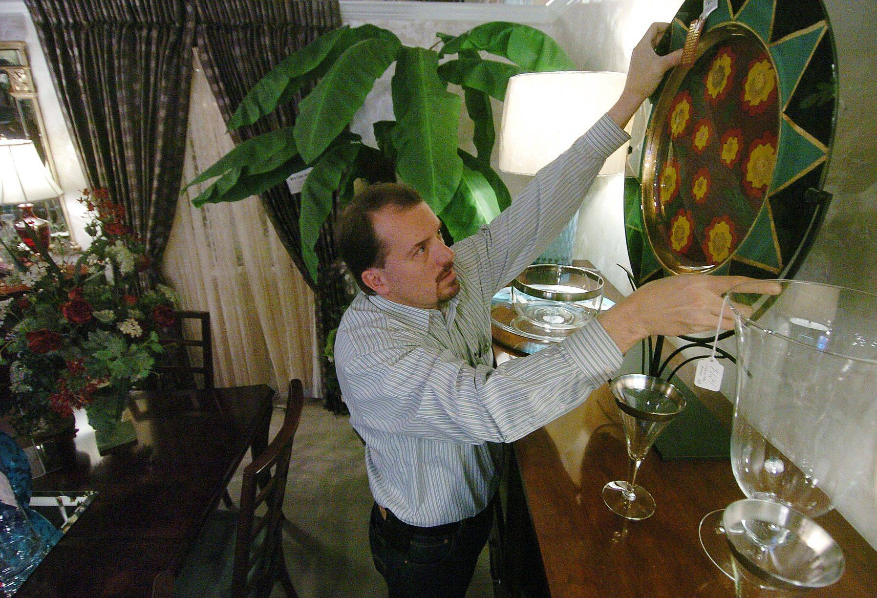 Mike Main, co-owner of Arden's furniture store, hangs a decorative platter for display. The business is closing after 37 years in downtown Libertyville.