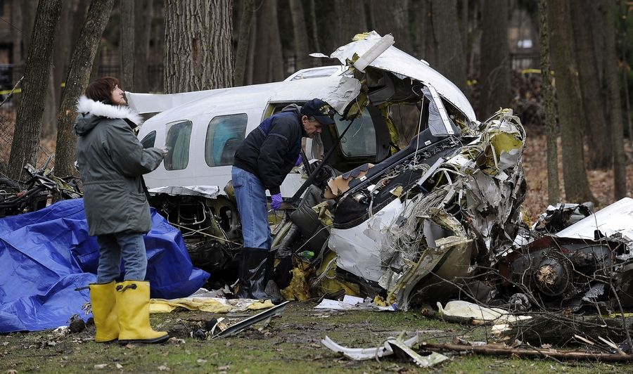 An official looks up to the trees where parts of the plane were caught by the branches when it crashed Monday night in Riverwoods and killed three people.