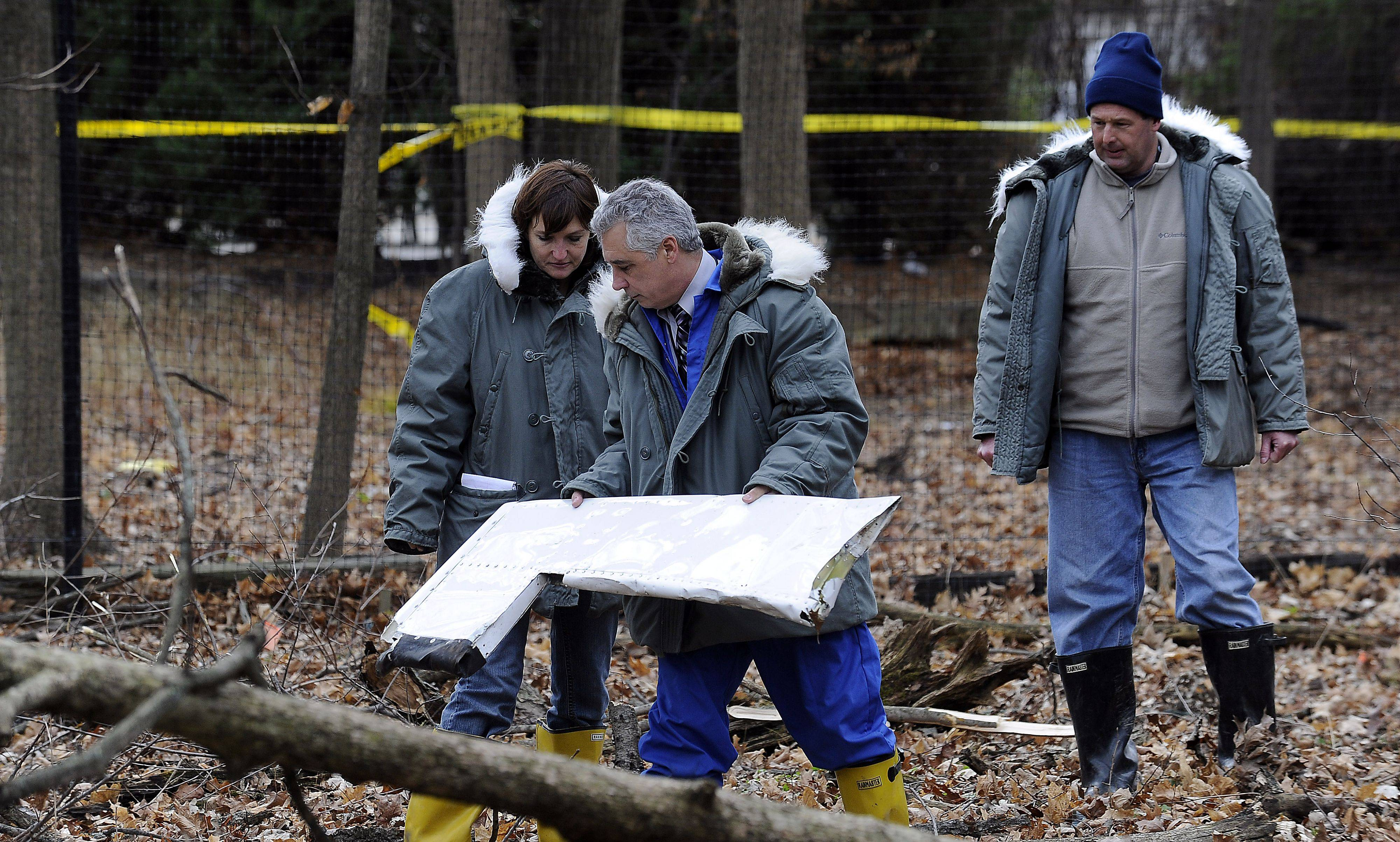 Officials from the FAA look over a section of the plane that crashed in Riverwoods, killing three people Monday.