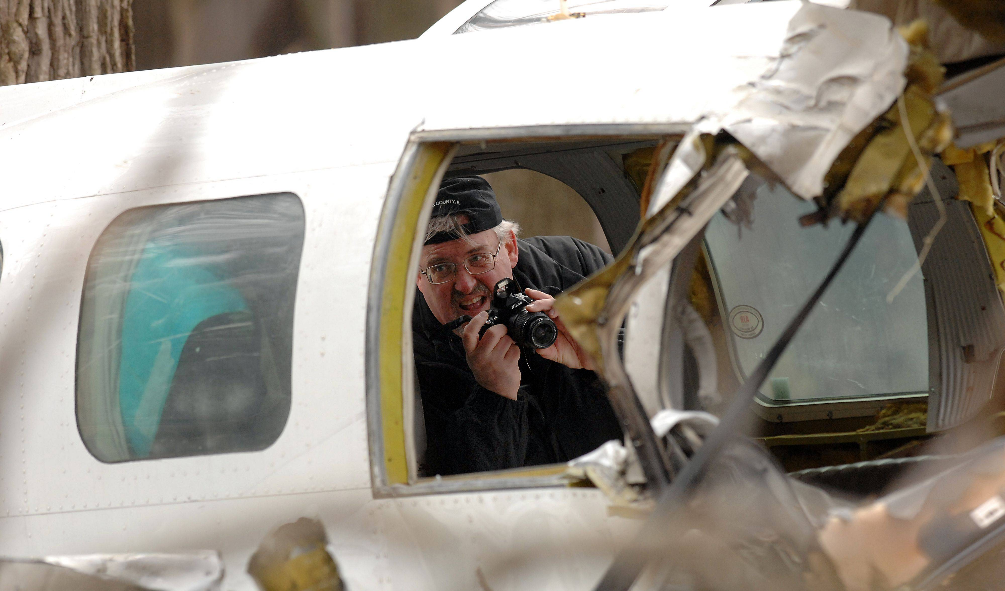 A FAA photographer takes pictures inside the wreckage of the plane that crashed in Riverwoods Monday night.