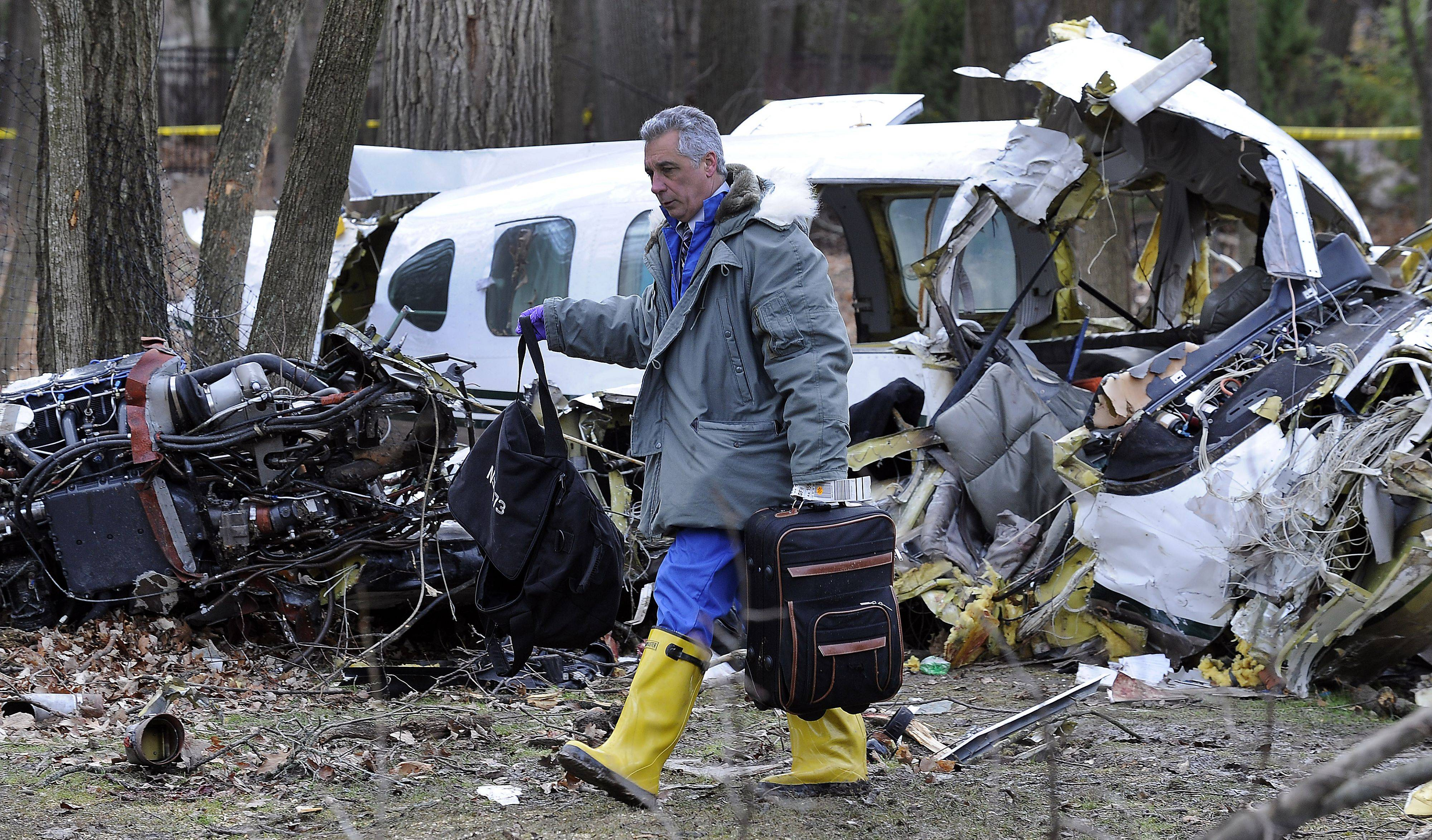 An official from the FAA carries away luggage from the Riverwoods' plane crash site.