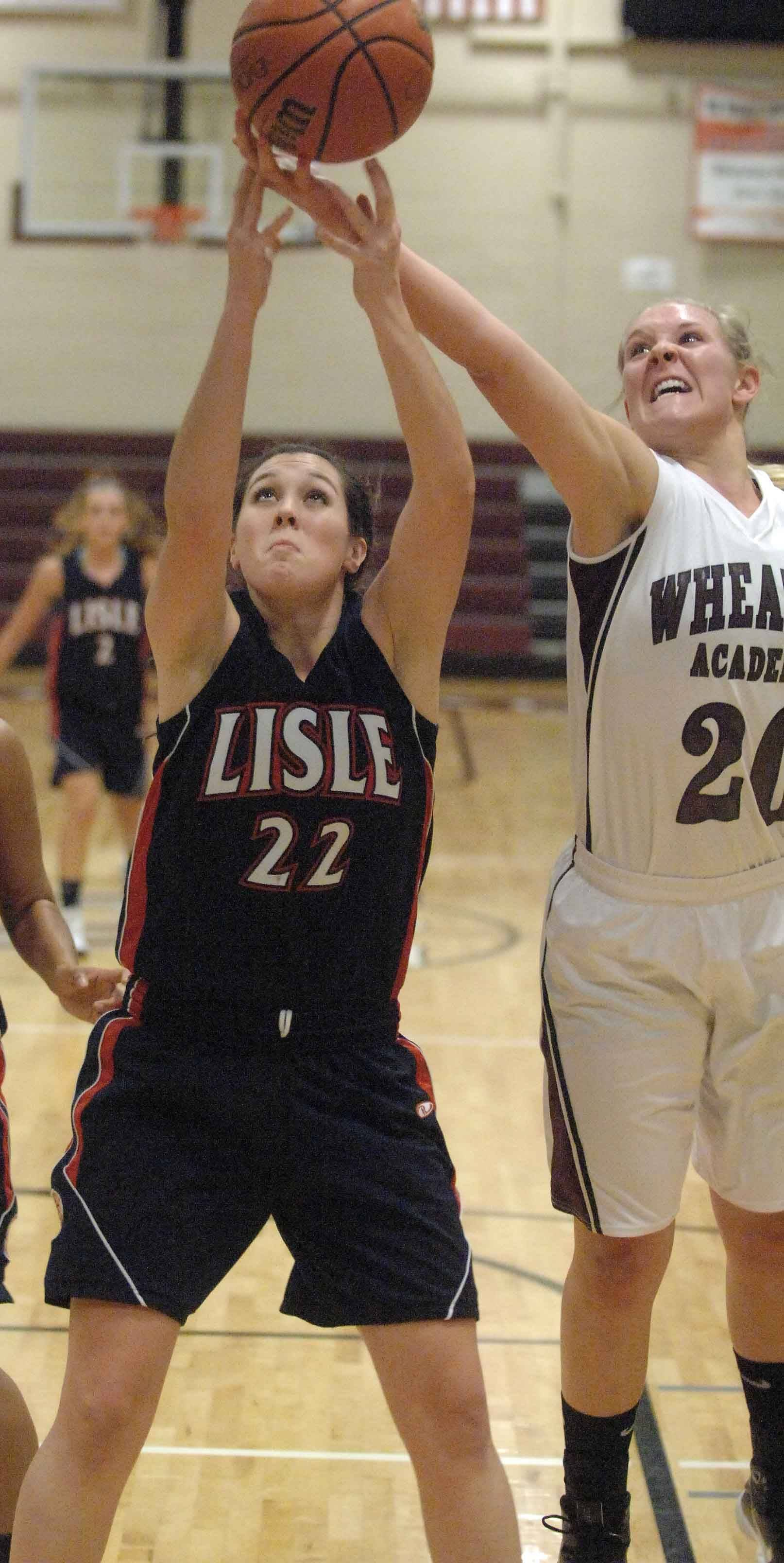 Shelby Kretman of Lisle, left, and Sarah Drury of Wheaton Academy, reach for a rebound Tuesday.