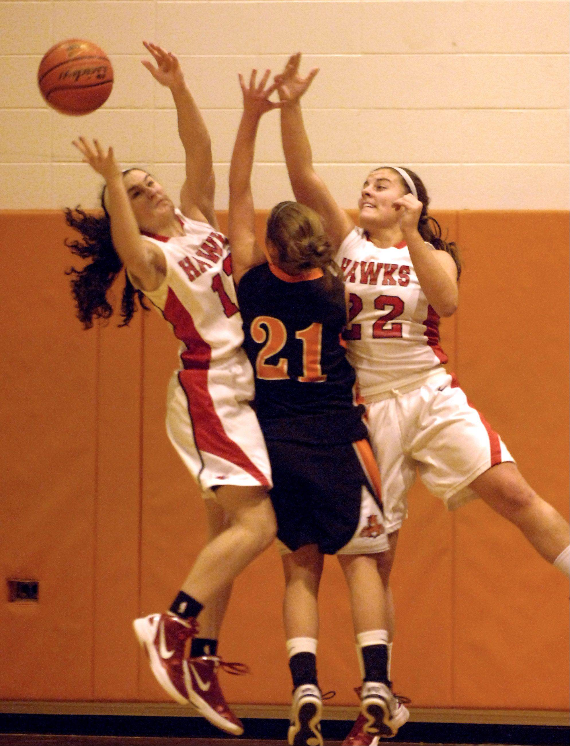 Libertyville's Olivia Mayer, 21, reaches for a rebound with Maine South's Regan Carmichael, left, and Nina Duric during Friday's Bison Classic 2011 girls basketball game in Buffalo Grove.