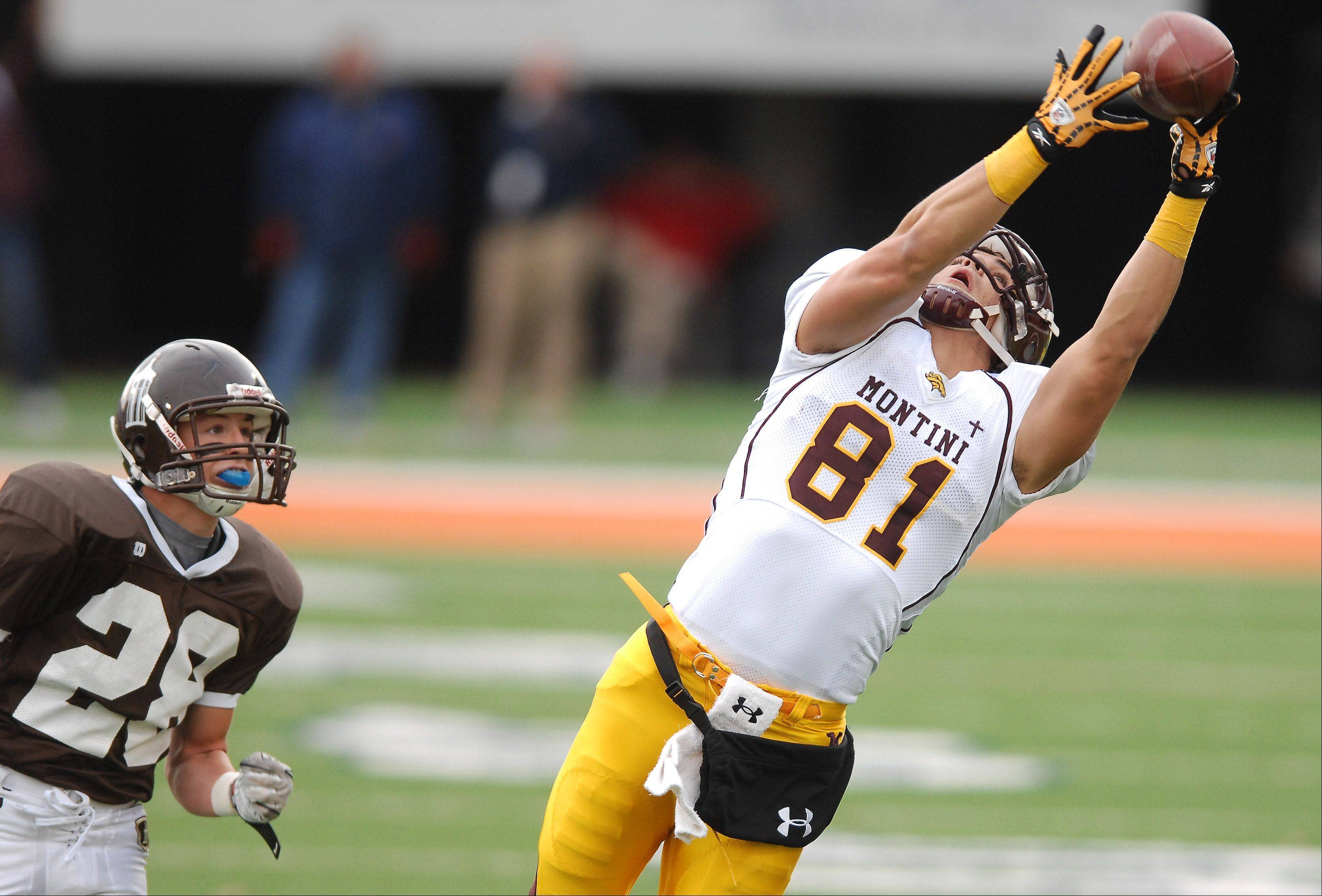 Montini's Jordan Westerkamp hauls in a long pass in front of Joliet Catholic Academy's Grant Harrison during the IHSA Class 5A state football championship game in Champaign Saturday.