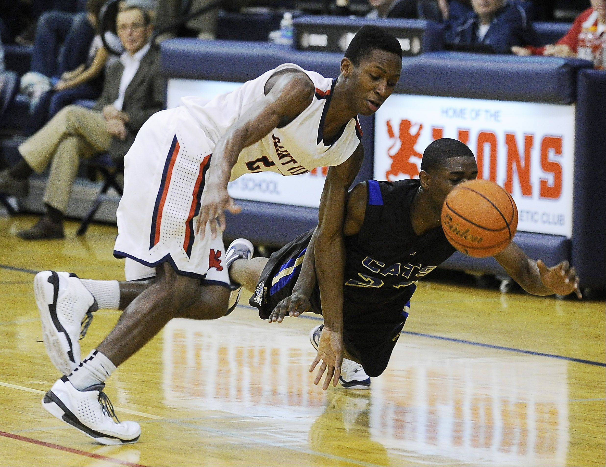 St.Viator's Ore Arogundade and Lamont McPherson of Wheeling chase down a loose ball in the Varsity Thanksgiving Basketball Tournament at St. Viator High School on Friday.