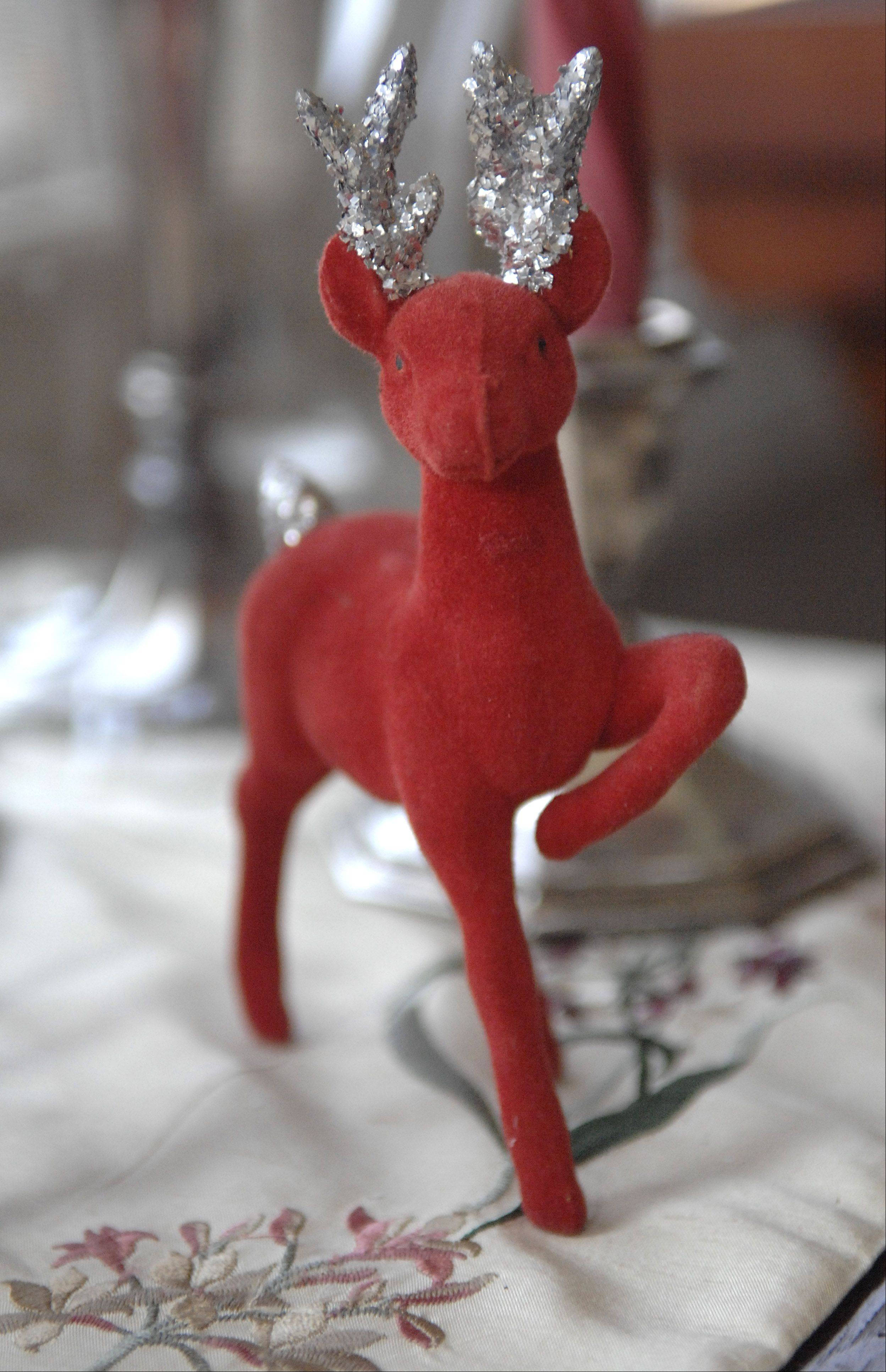 An antique felted reindeer decoration sits on a table in Patricia Harkin's Elgin home, which is featured on the Homes for the Holidays House Walk. Harkin says she gets many of her decorations from resale shops.