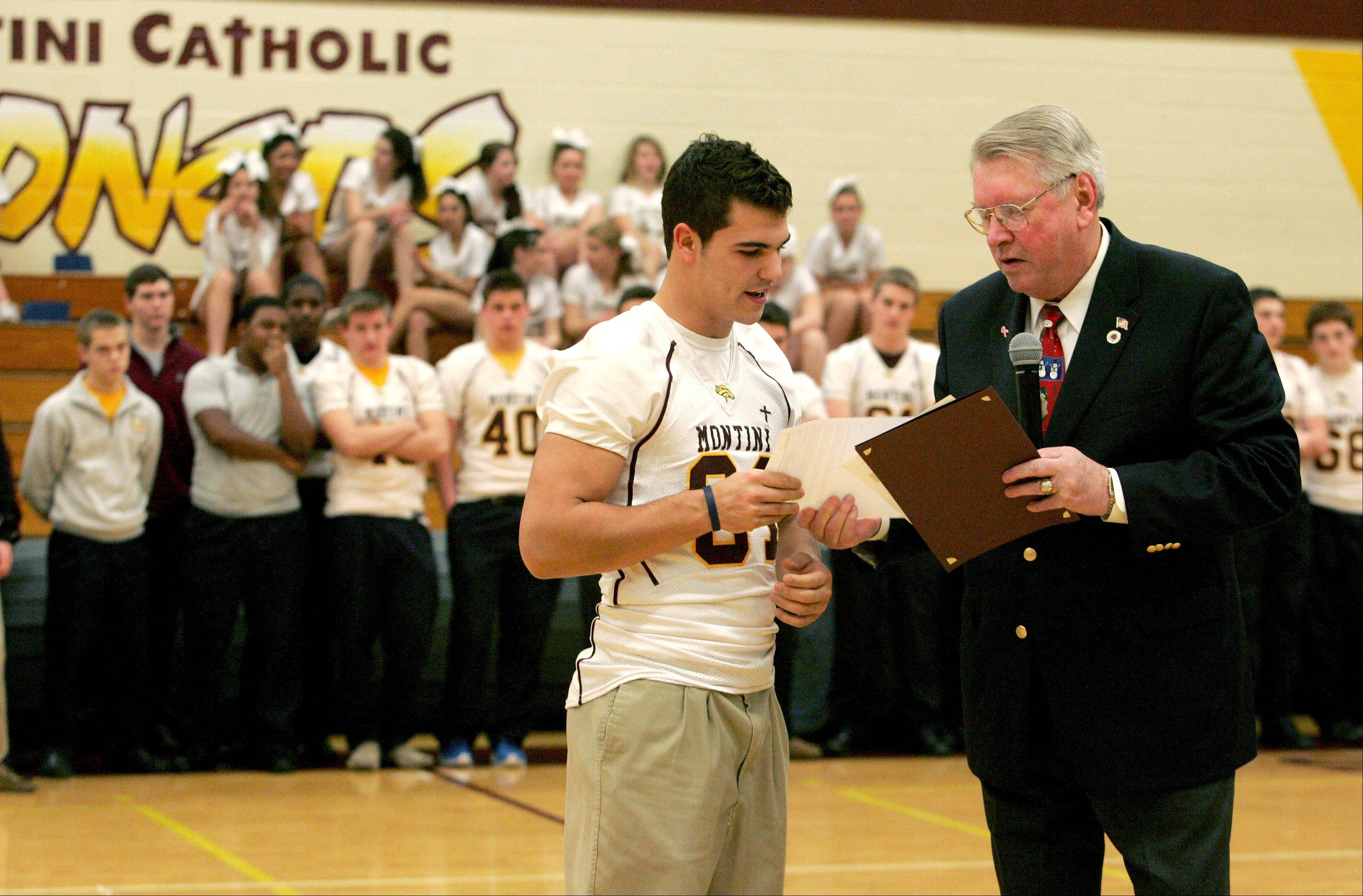 Lombard Village President Bill Mueller hands Montini senior wide receiver Jordan Westerkamp a copy of an email from Glen Ellyn Village President Mark Pfefferman praising Westerkamp and the Montini football team during a pep rally Friday celebrating the team's third consecutive Class 5A state championship.