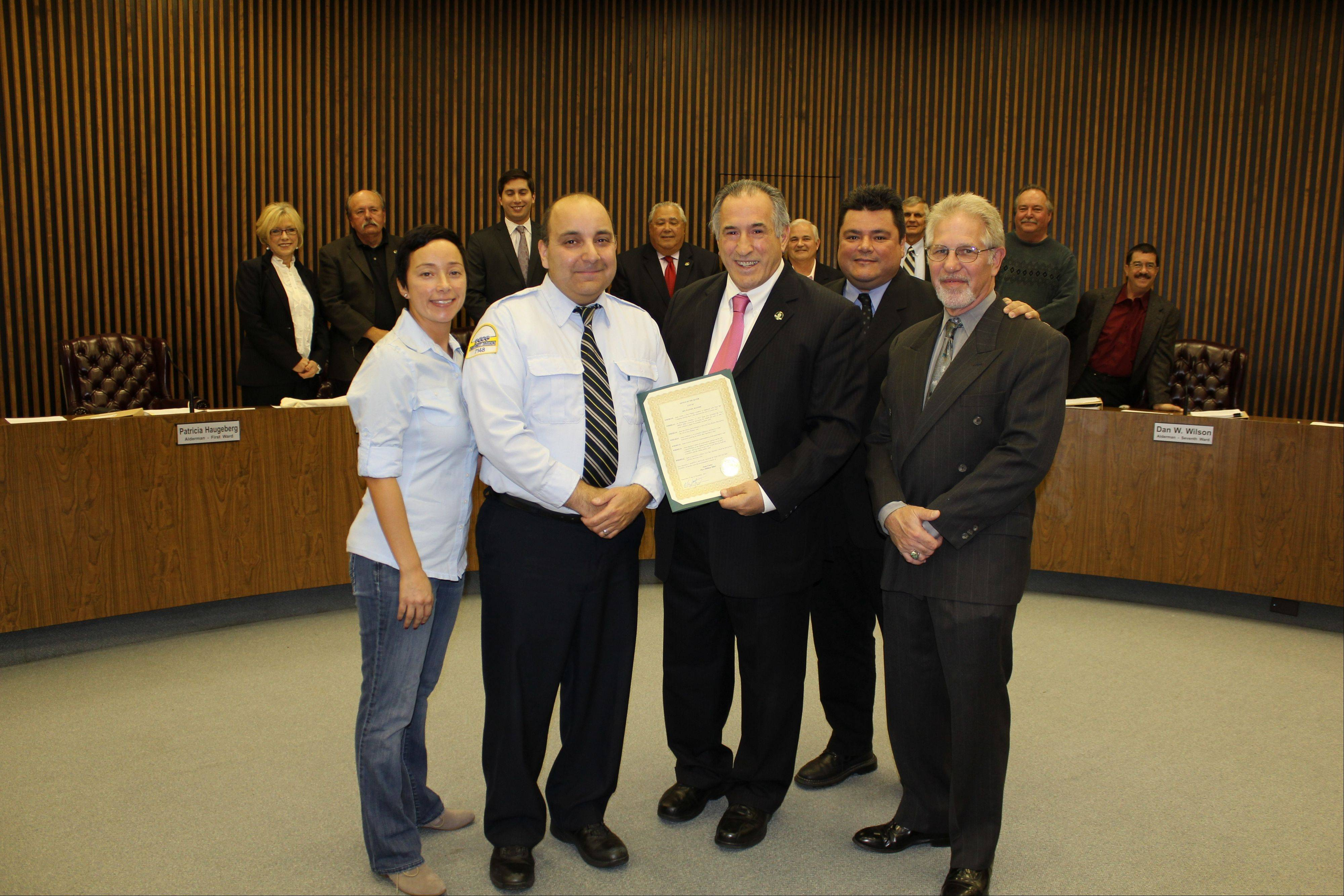 Pictured, from left, are: Front row: Gina Cortez, Juan Cortez, Mayor Moylan, Pace Assistant Superintendent of Transportation James Barsano and Pace safety and training manager Mike Strauss; back row: 1st Ward Alderman Patricia Haugeberg, 2nd Ward Alderman John Robinson, 3rd Ward Alderman Matt Bogusz, 4th Ward Alderman Dick Sayad, 5th Ward Alderman James Brookman, 7th Ward Alderman Dan W. Wilson, 6th Ward Alderman Mark Walsten, and 8th Ward Alderman Mike Charewicz.