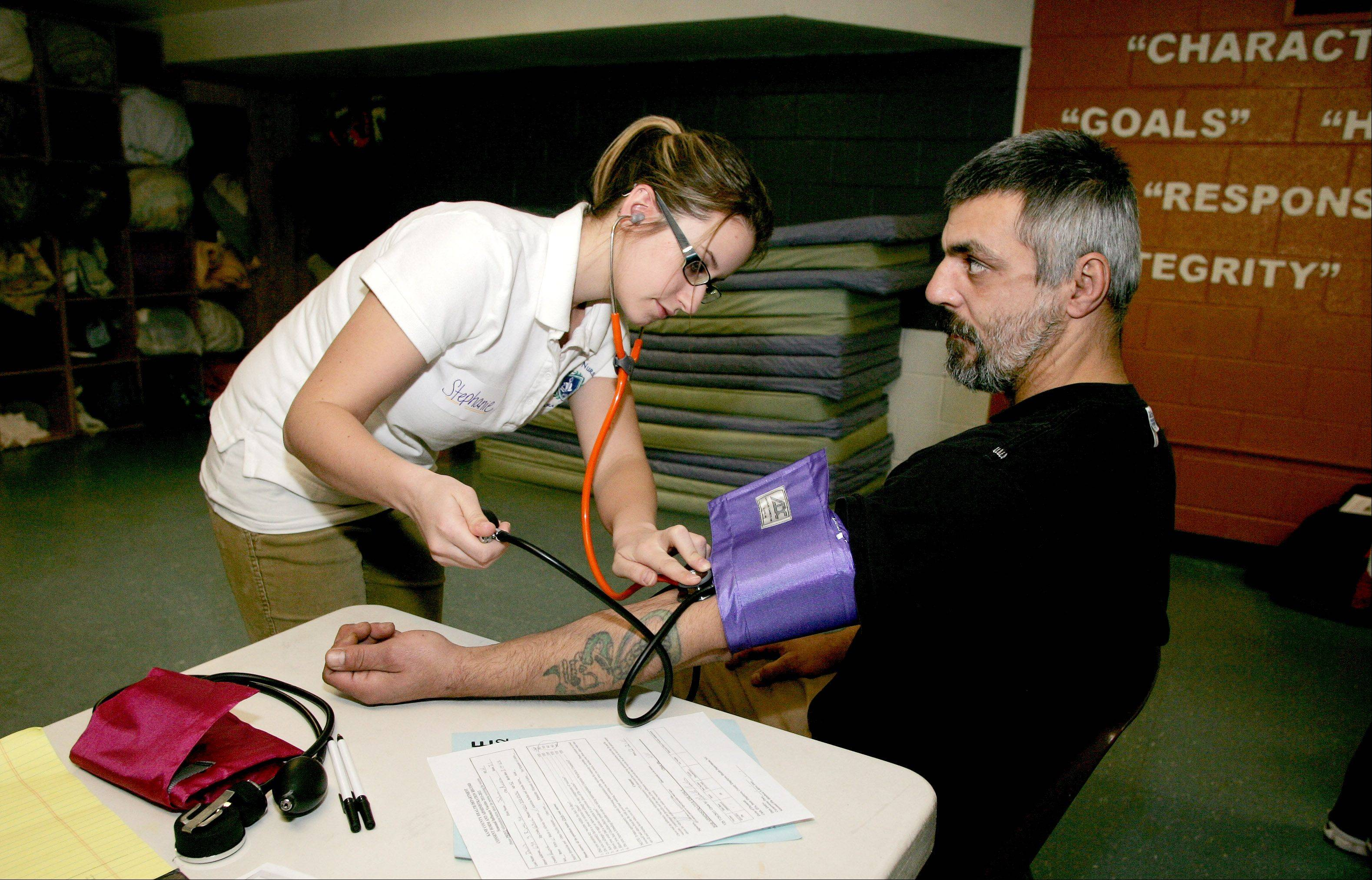 John Davis, who stays at Hesed House in Aurora, has his blood pressure taken Friday by nursing student Stephanie Peterson as Aurora University nursing students hold their first health clinic at the homeless services center.