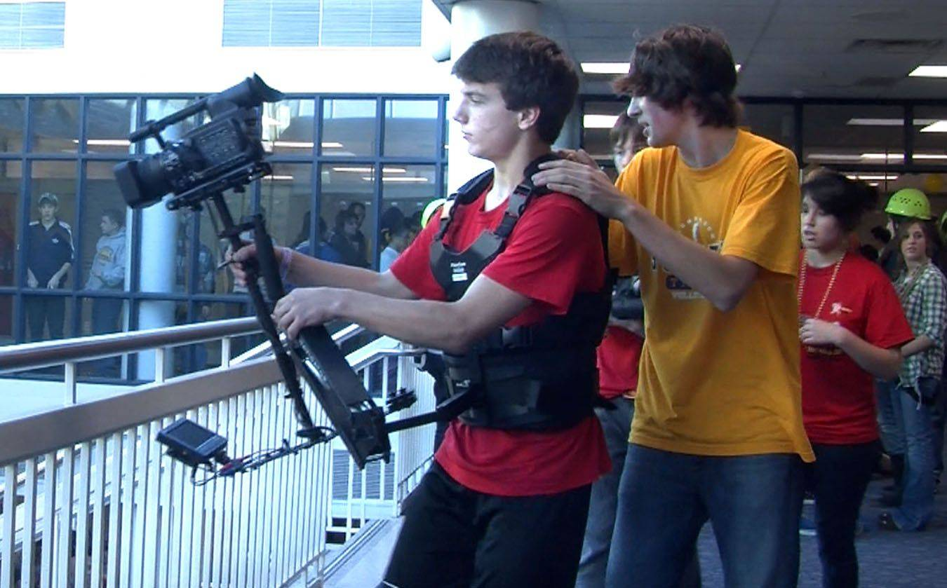 Glenbrook South High School student cameraman John Paul O'Rourke is guided by Kevin Mathein while videotaping the school's 50th anniversary video, which features the entire school.