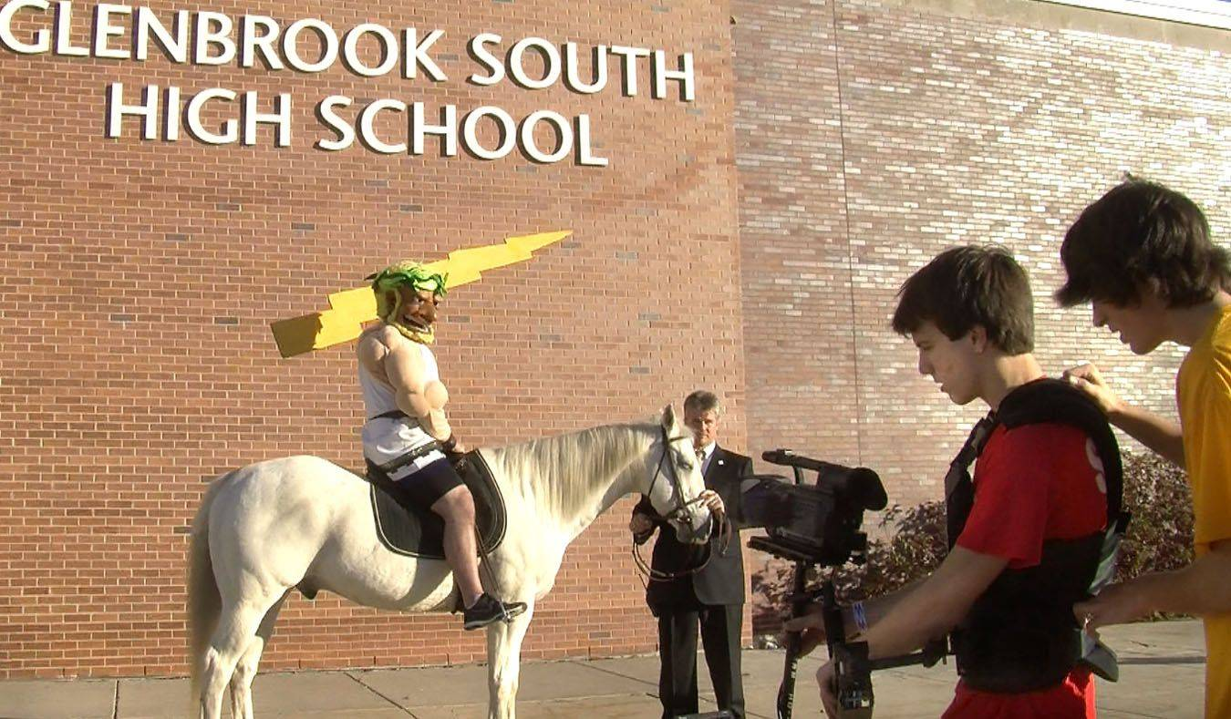 "Glenbrook South High School student cameraman John Paul O'Rourke is guided by Kevin Mathein while videotaping the school's mascot on a rented horse for taping of the school's 50th anniversary ""Lip Dub"" video."