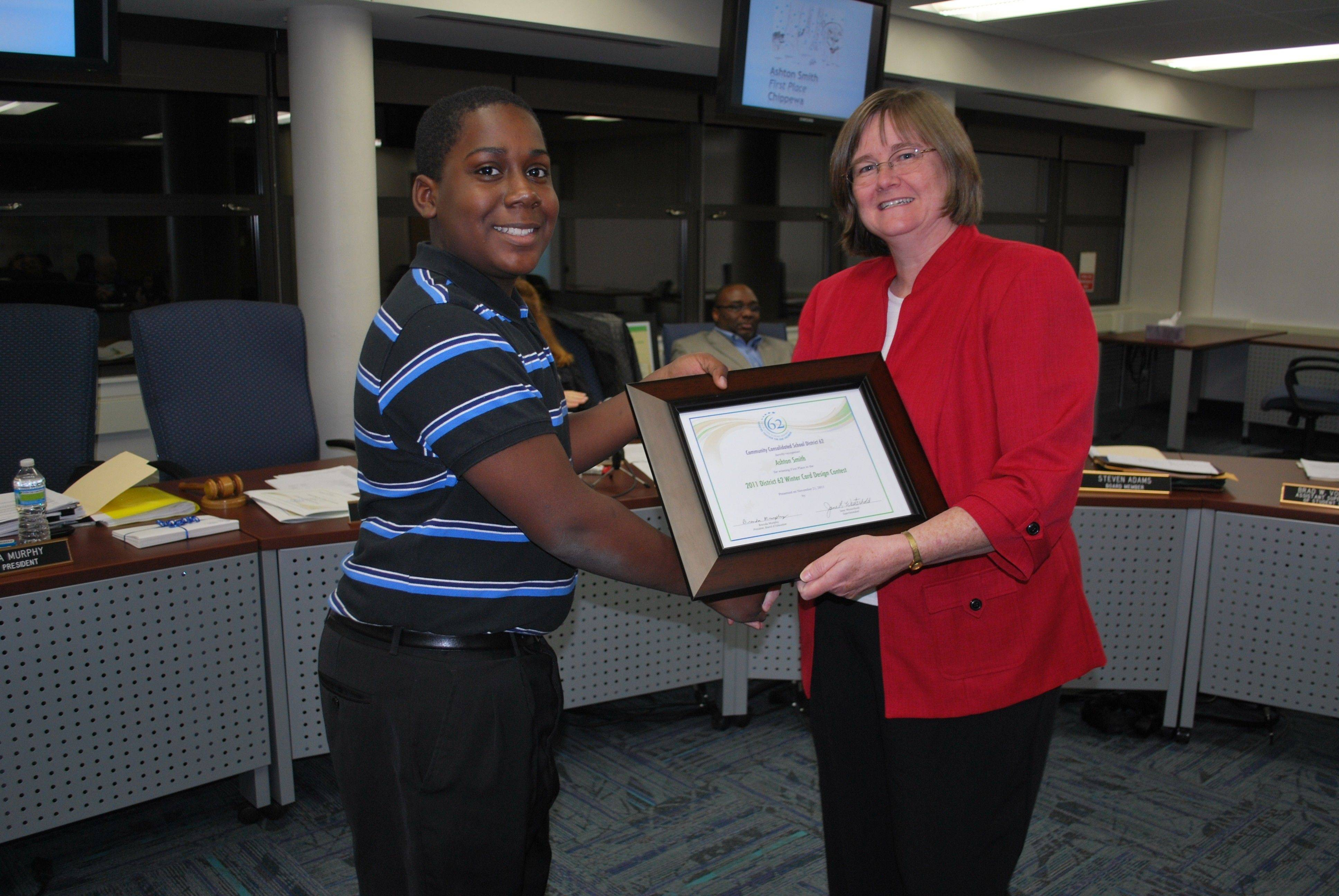 District 62 Winter Card Design Contest winner Ashton Smith accepts a Certificate of Recognition from board President Brenda Murphy.